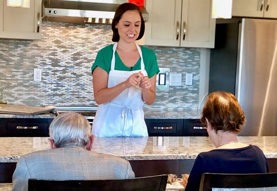 Registered dietitian Gisela Bouvier, assists Moorings Park at Grey Oaks memory care residents create bread.