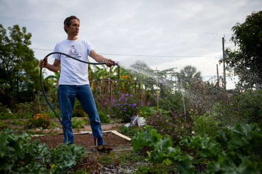 Sean McCabe waters a bed at a community garden on 98th Avenue North in Naples Park on Tuesday, May 7, 2019. McCabe lives across the street from the garden.
