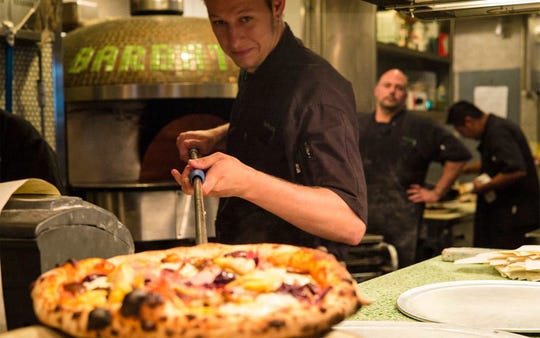 Corporate Chef Jason Goddard presents one of Barbatella's wood-fired pizzas in downtown Naples.