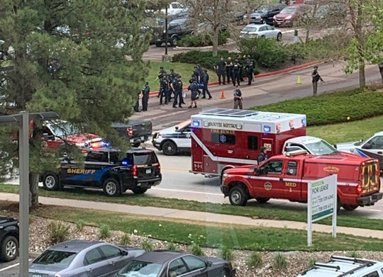Armed police officers and others are seen outside STEM School Highlands Ranch, a charter middle school in the Denver suburb of Highlands Ranch, Colo., after a shooting Tuesday, May 7, 2019.  (Courtney Harper via AP)