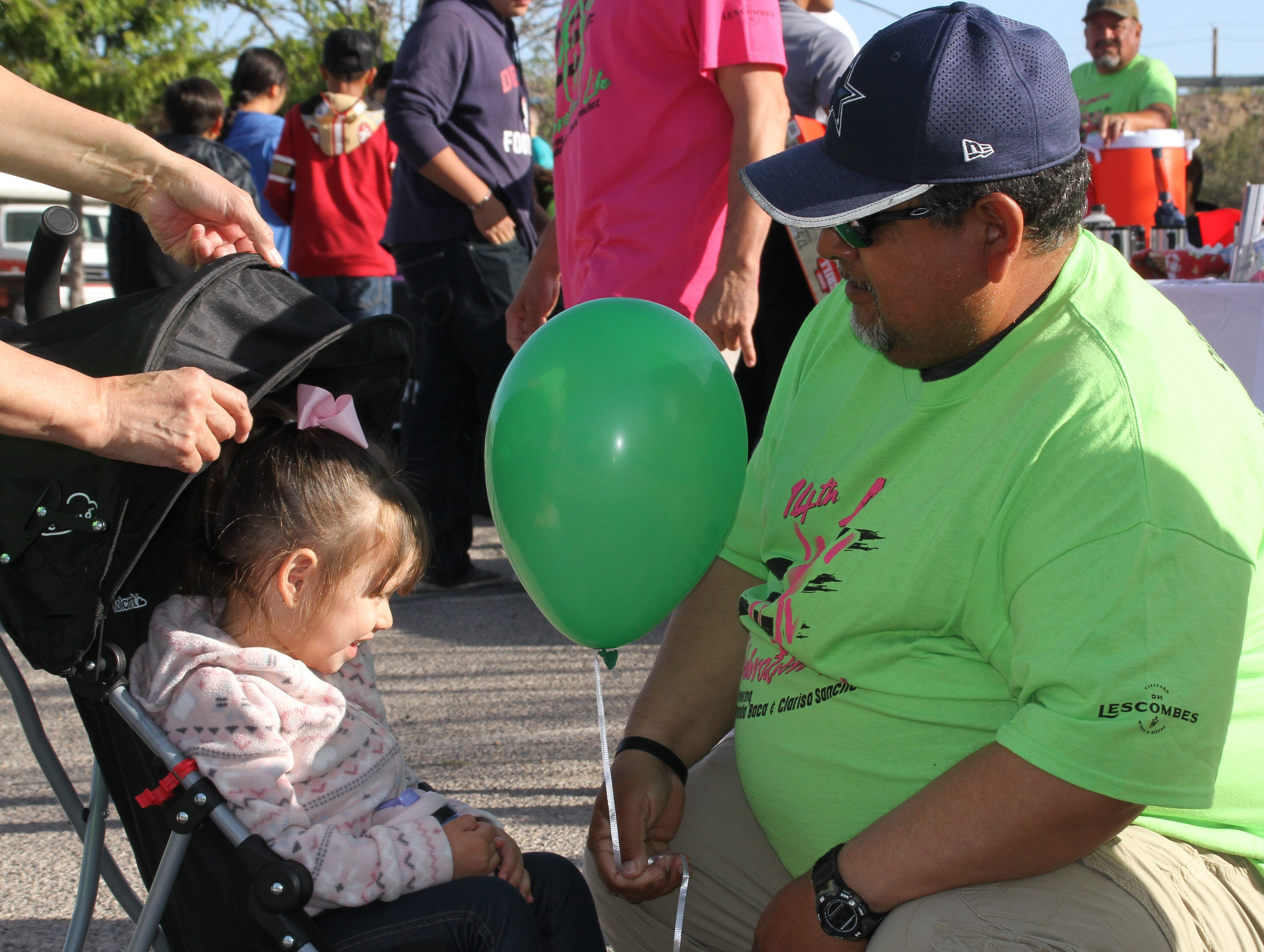 Pete Alvarado presenting his granddaughter Jazay Nordorf, 2, a balloon.