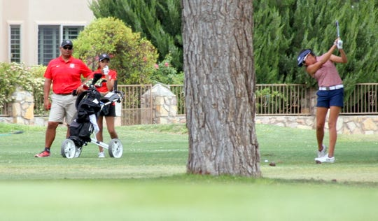 Lady 'Cat junior Mona Magana (far right) takes a practice swing before her approach to the No. 9 green.