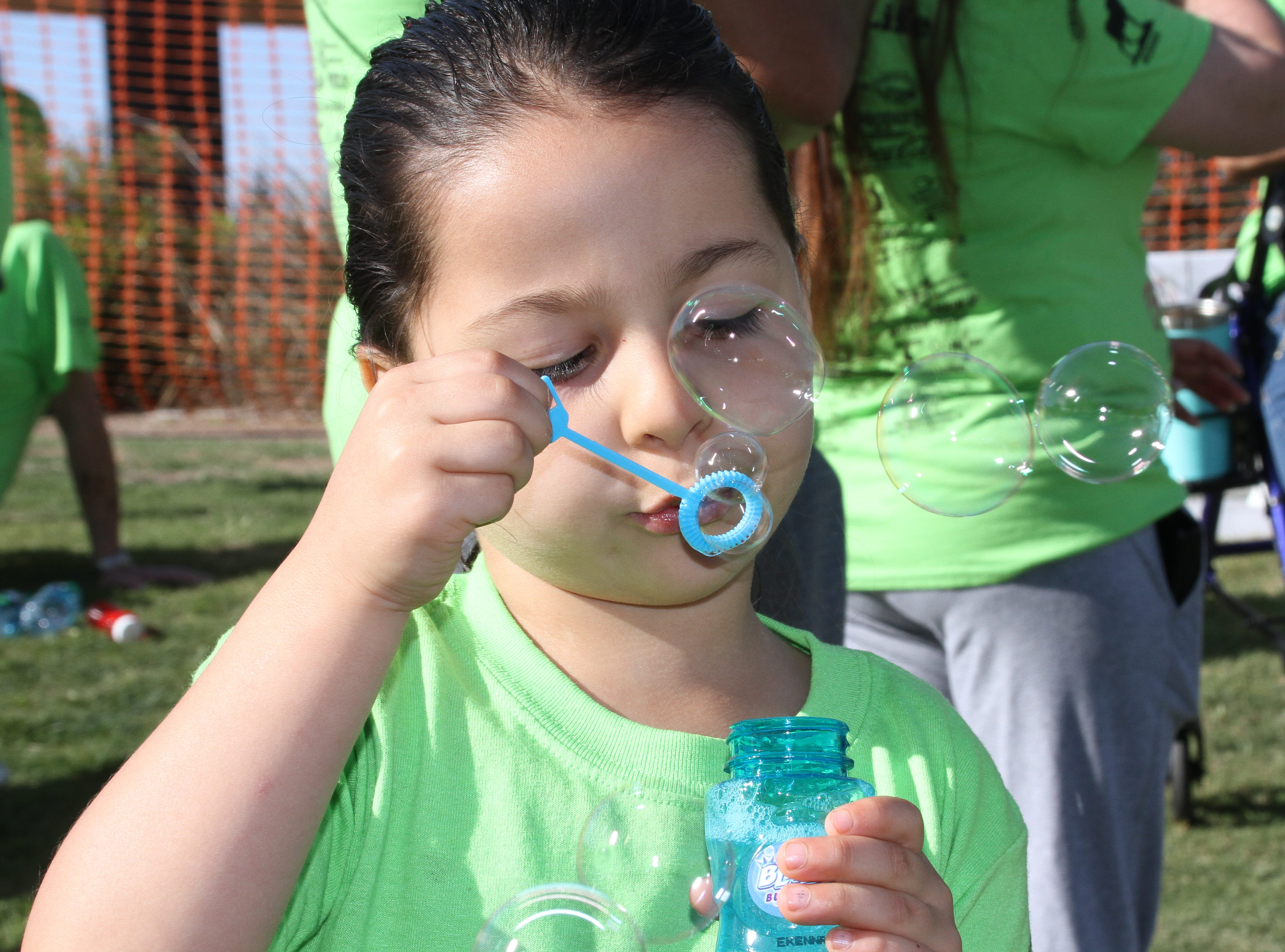 Four-year-old Natalia Rivera blowing bubbles.