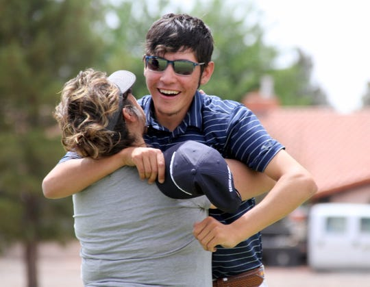 Senior Wildcat golfer Nemo Perales gets a big hug from his mother Yvonne Jasso Perales on the 18th green after completing his final high school round on the Rio Mimbres course. Perales successfully defended his District 3-5A championship and led the varsity to the team title.