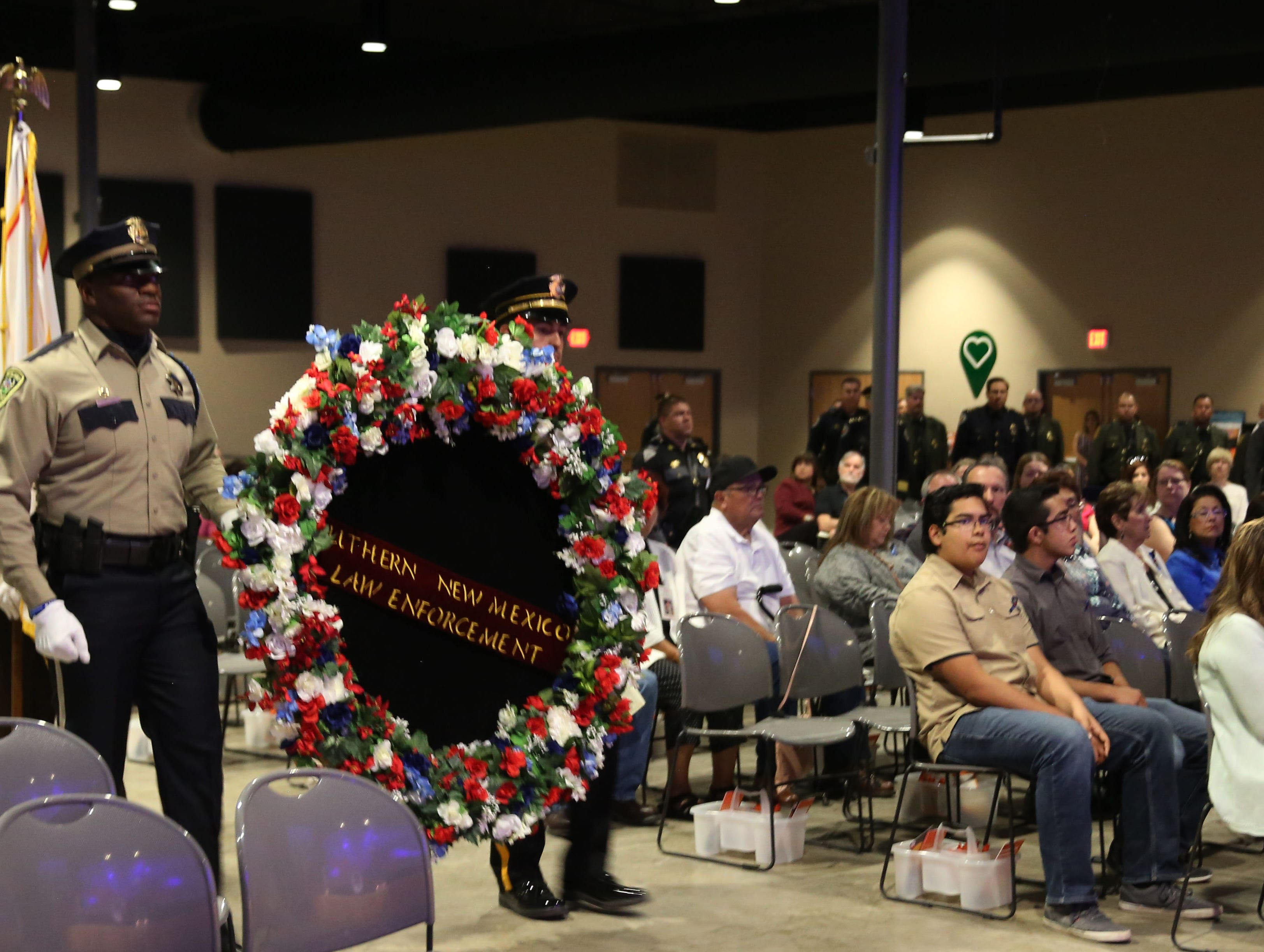 Officers walk a memorial wreath into the Fallen Officer Memorial, Tuesday May 7, 2019, at Mesilla Park Community Church.