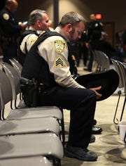 Chaves County Deputy Sgt. James Mason bows his head in a moment of silence Tuesday May 7, 2019, at the Fallen Officer Memorial in Las Cruces.