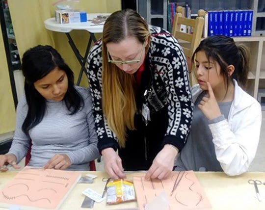 Hidalgo Medical Services medical resident Dr. Susan Bauer teaches the basics of suturing wounds to La Plata Dream Makers Alina Ortiz, left, and Deziraye Salgado.