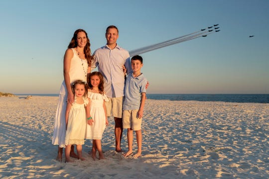 A family portrait on Orange Beach, Alabama, with the Blue Angels flying over.