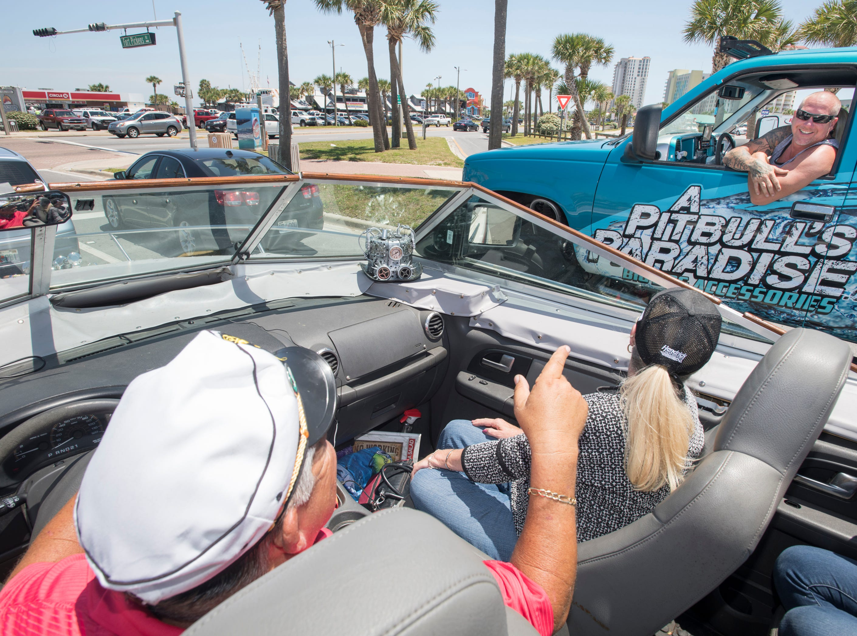 Gerry and Karen Moore chat with Tim Vaughn, right, about their Boat Car while stopped at a red light  in Pensacola Beach on Tuesday, May 7, 2019.  The vehicle is a 1986 Chris Craft 210 Scorpion boat - 2003 Ford Expedition SUV hybrid created by Gerry.