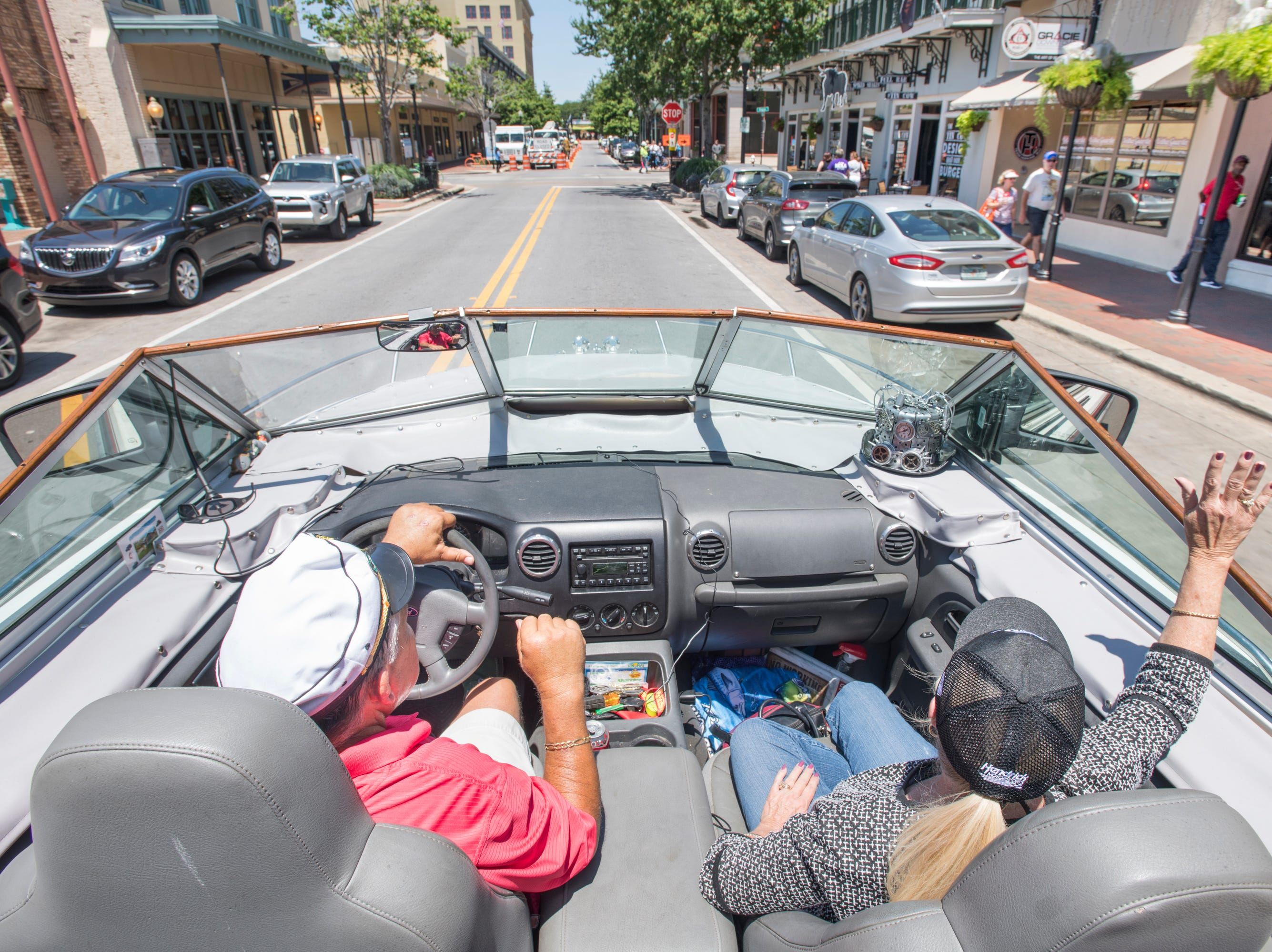 Gerry and Karen Moore wave to passers-by as they cruise along Palafox Street in their Boat Car in downtown Pensacola on Tuesday, May 7, 2019.  The vehicle is a  1986 Chris Craft 210 Scorpion boat - 2003 Ford Expedition SUV hybrid created by Gerry.