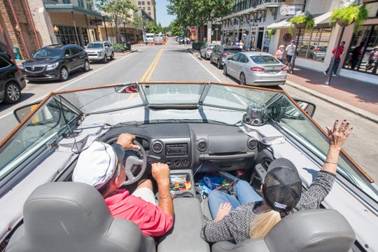 Gerry and Karen Moore wave to passersby Tuesday as they cruise in their boat car along Palafox Street in downtown Pensacola.