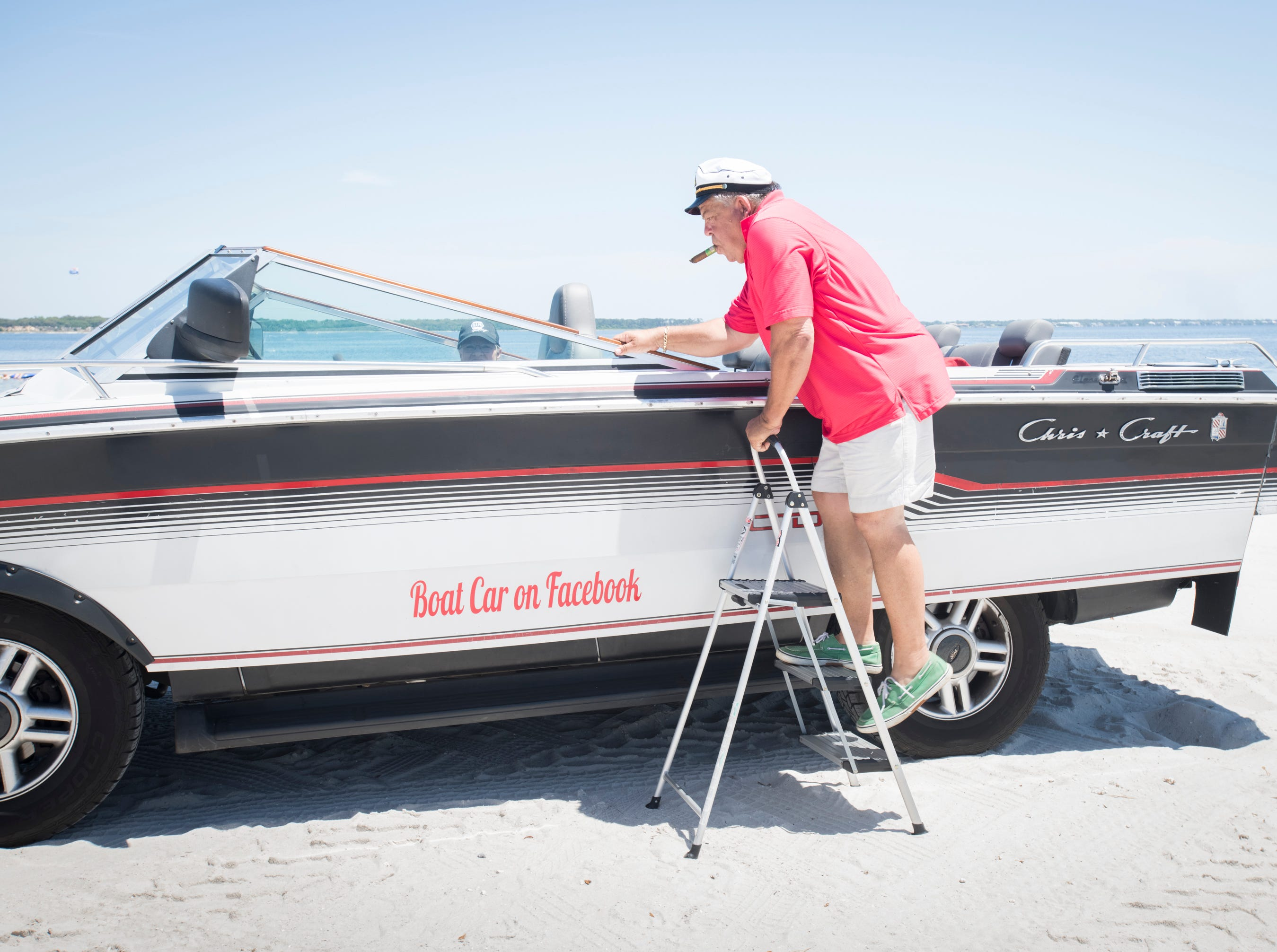 Gerry Moore climbs aboard his Boat Car at Quietwater Beach in Pensacola on Tuesday, May 7, 2019.  The vehicle is a 1986 Chris Craft 210 Scorpion boat - 2003 Ford Expedition SUV hybrid created by Gerry.