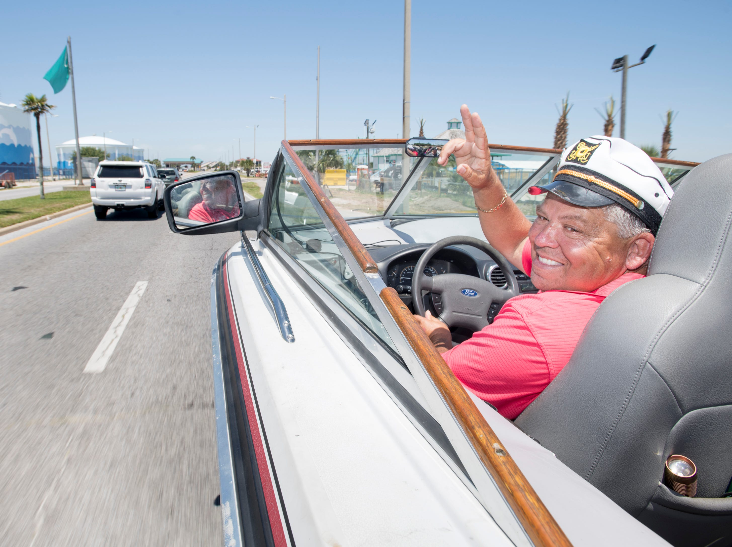 Gerry Moore waves to passing cars as he cruises along Pensacola Beach Blvd. in his Boat Car in Pensacola on Tuesday, May 7, 2019.  The vehicle is a  1986 Chris Craft 210 Scorpion boat - 2003 Ford Expedition SUV hybrid created by Gerry.