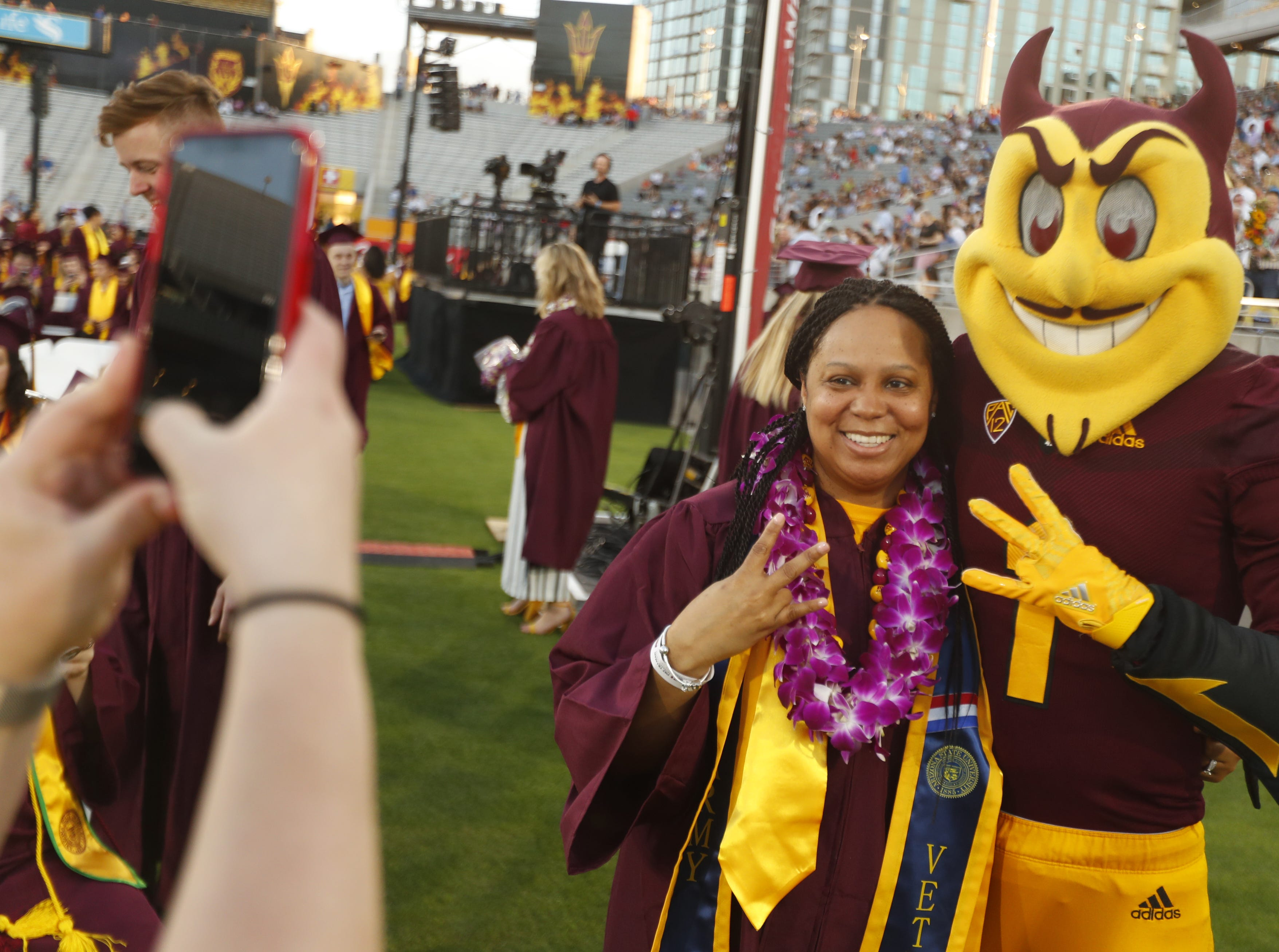ASU's Cherise Shockley poses for a picture with Sparky during ASU's Undergraduate Commencement at Sun Devil Stadium in Tempe, Ariz. on May 6, 2019.
