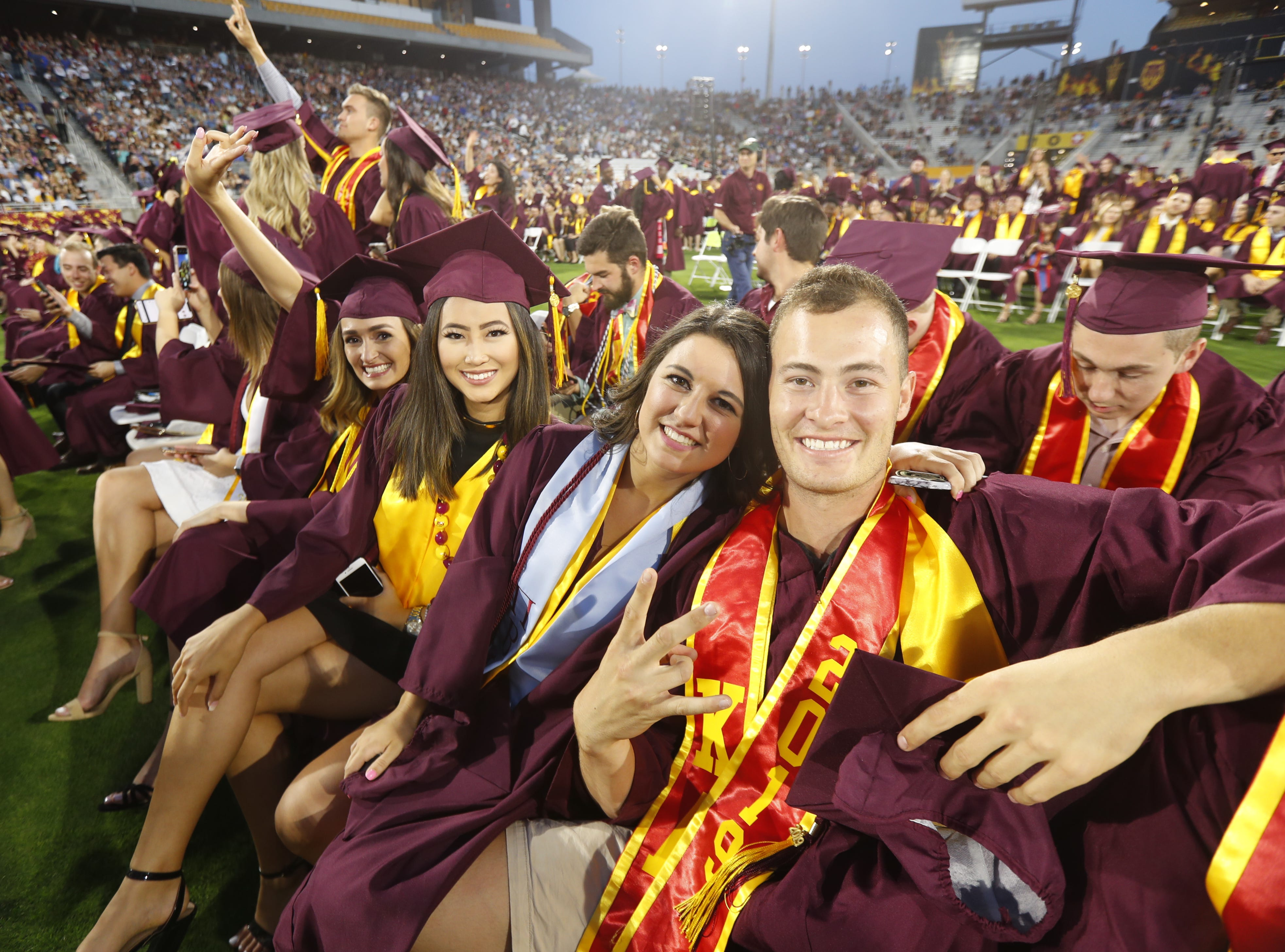 ASU graduates pose for pictures before ASU's Undergraduate Commencement at Sun Devil Stadium in Tempe, Ariz. on May 6, 2019.
