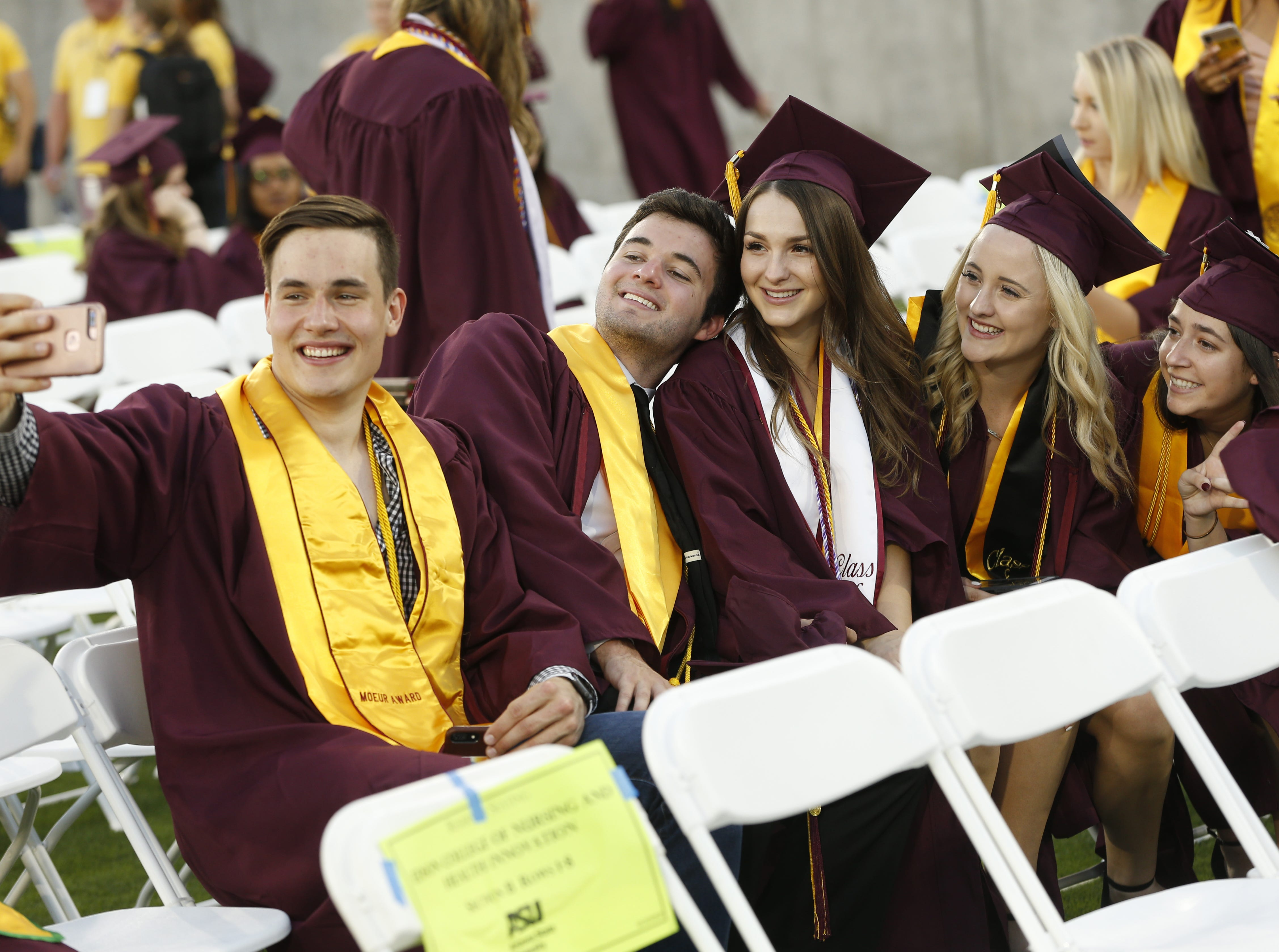 ASU graduates take selfies before ASU's Undergraduate Commencement at Sun Devil Stadium in Tempe, Ariz. on May 6, 2019.