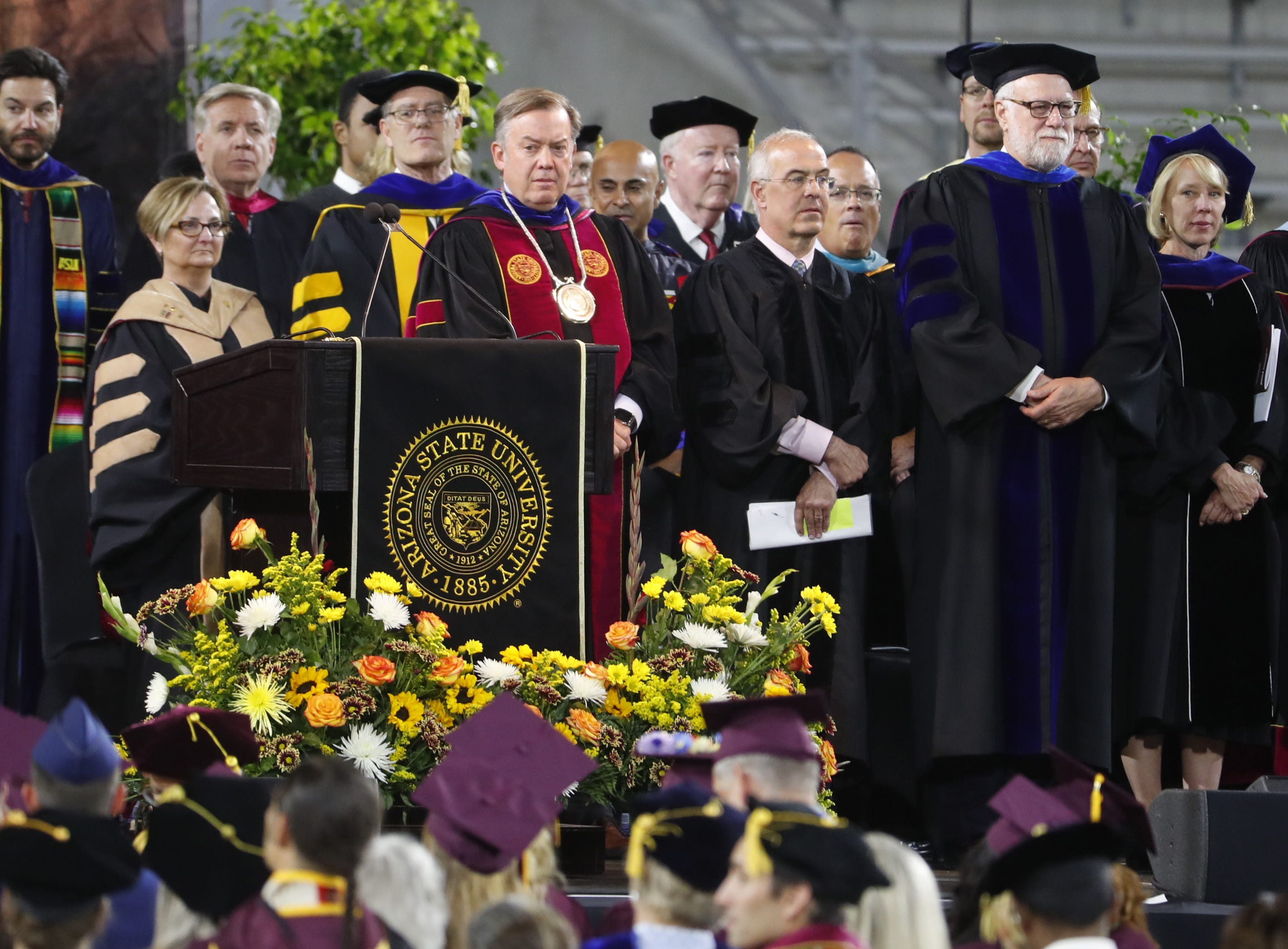ASU President Michael Crow stands with Reagents during ASU's Undergraduate Commencement at Sun Devil Stadium in Tempe, Ariz. on May 6, 2019.