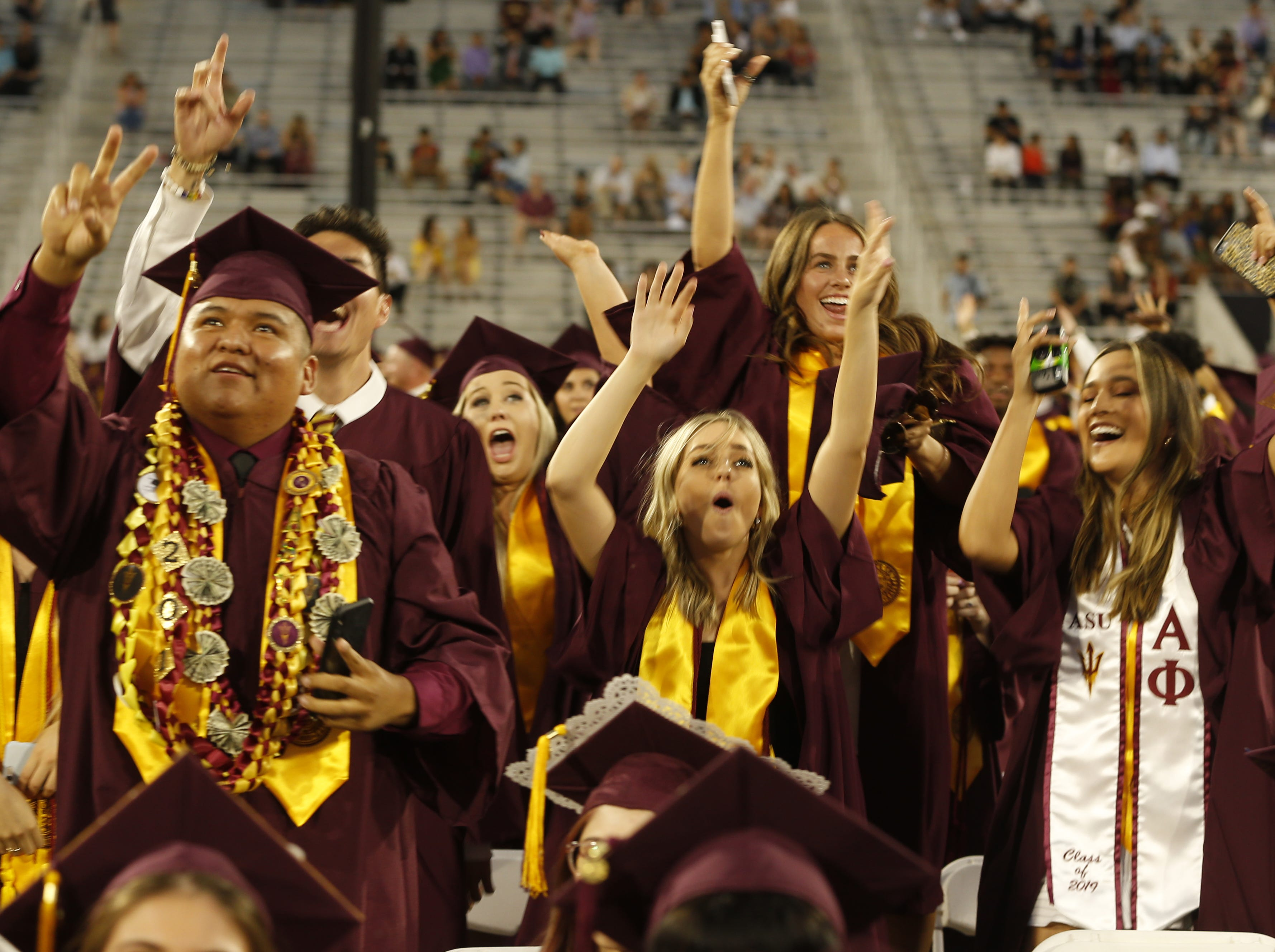 ASU graduates react as they are put on the big screen during ASU's Undergraduate Commencement at Sun Devil Stadium in Tempe, Ariz. on May 6, 2019.