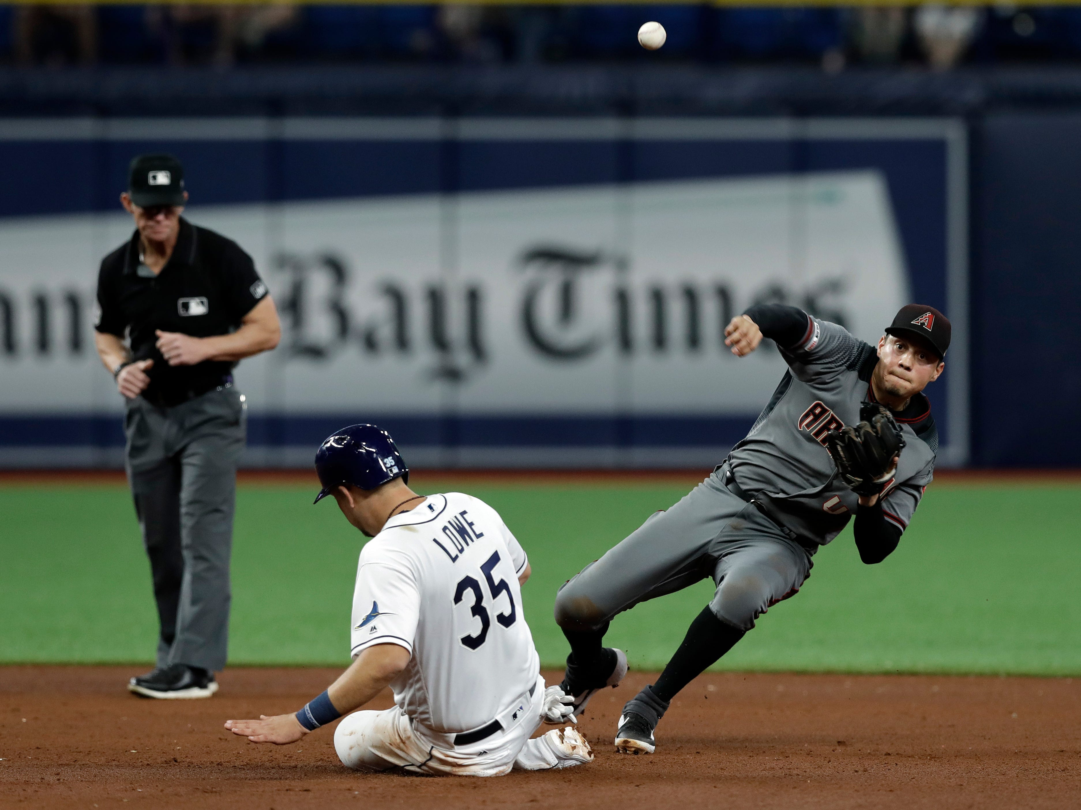 Arizona Diamondbacks second baseman Wilmer Flores, right, falls as he forces Tampa Bay Rays' Nate Lowe (35) on a fielder's choice by Avisail Garcia during the fifth inning of a baseball game Monday, May 6, 2019, in St. Petersburg, Fla. (AP Photo/Chris O'Meara)