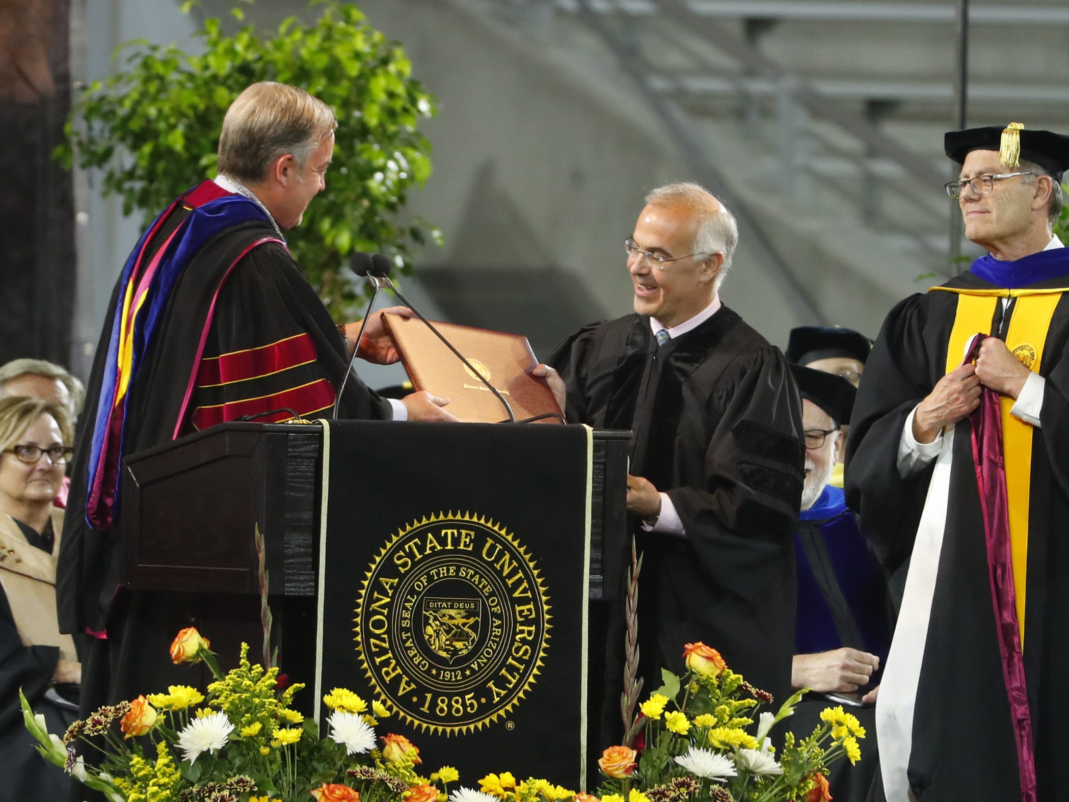 ASU President Michael Crow presents David Brooks with an honorary degree during ASU's Undergraduate Commencement at Sun Devil Stadium in Tempe, Ariz. on May 6, 2019.