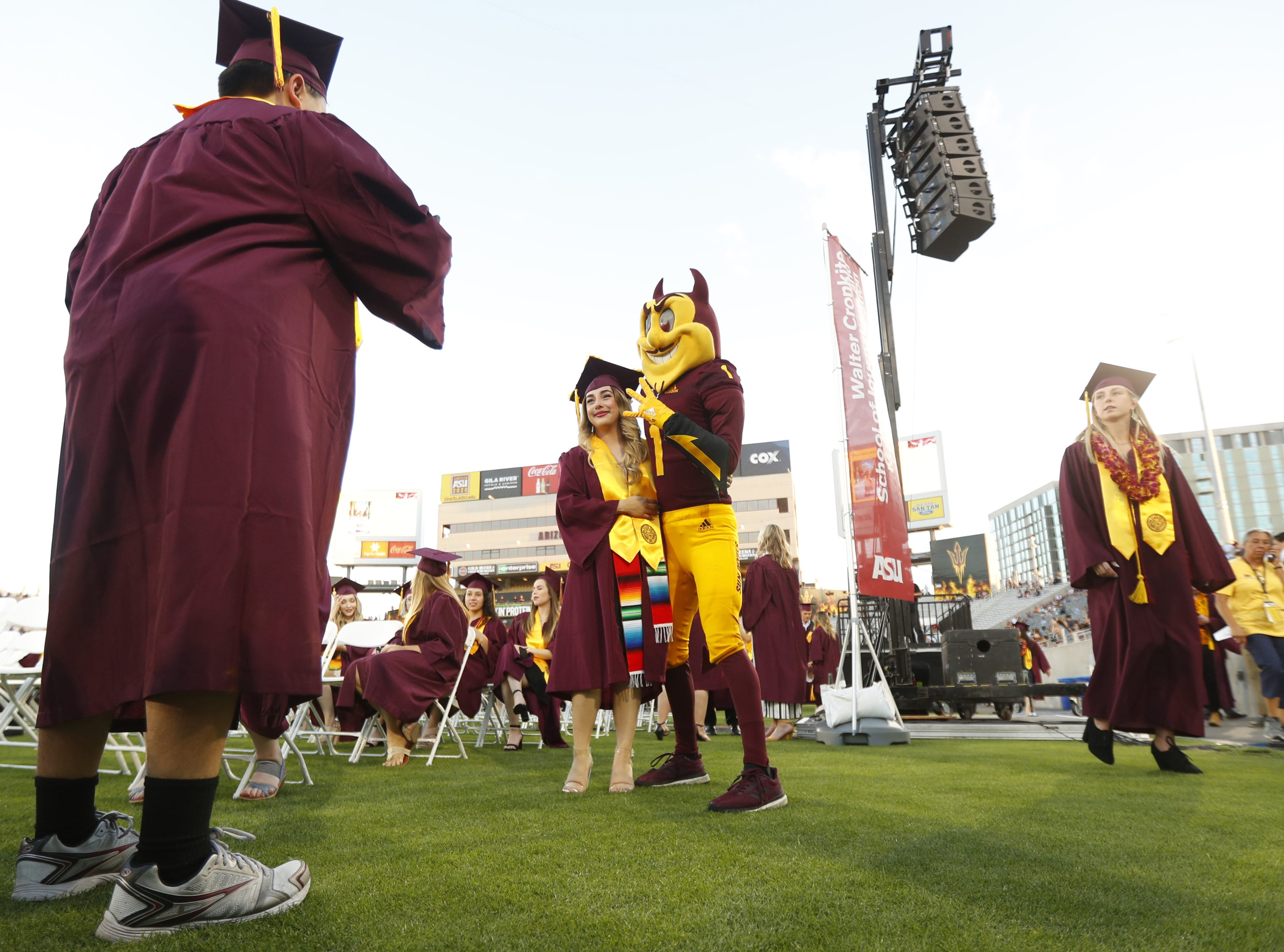 ASU graduates take pics with Sparky during ASU's Undergraduate Commencement at Sun Devil Stadium in Tempe, Ariz. on May 6, 2019.