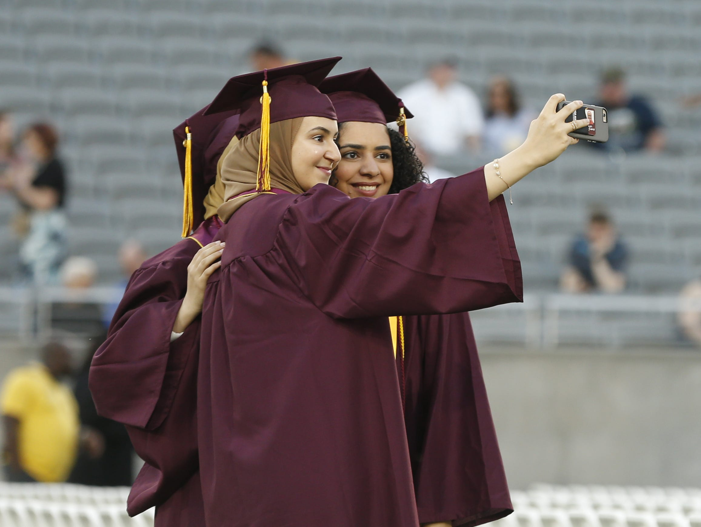 ASU graduates' Mayar Allam (front), Maria Hanna (R) and Israa Abdelaziz (back) pose for a picture during ASU's Undergraduate Commencement at Sun Devil Stadium in Tempe, Ariz. on May 6, 2019.