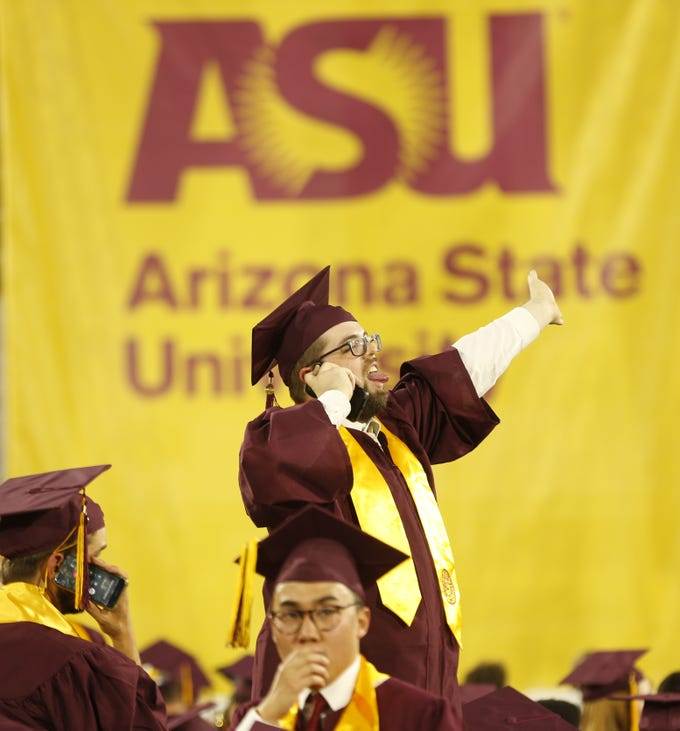 ASU graduates wave to friends and family before ASU's Undergraduate Commencement at Sun Devil Stadium in Tempe, Ariz. on May 6, 2019.