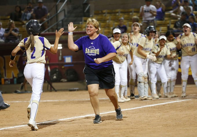 Sabino's Hannah Stark (2) is congratulated by Sabino head coach Chris Stainer after hitting a solo home run against Snowflake in the 3A softball state championship game in Tempe May 6, 2019.