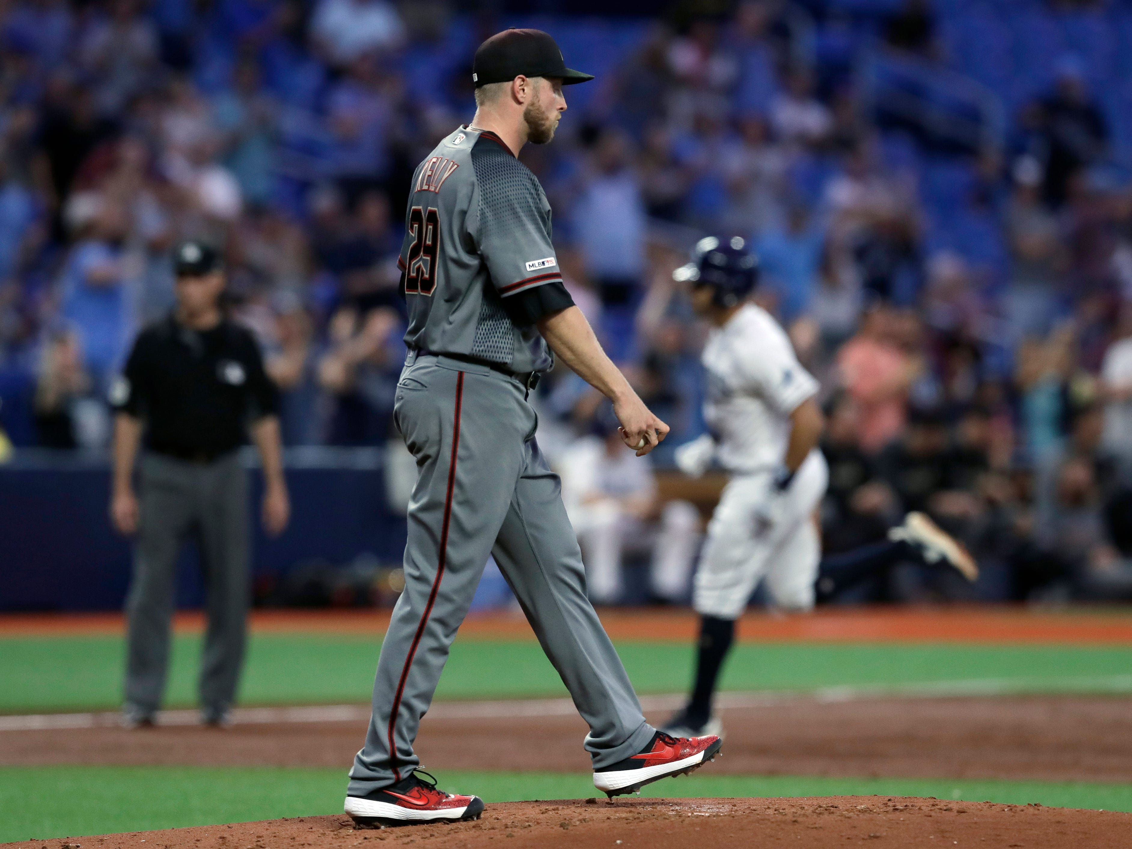Arizona Diamondbacks starting pitcher Merrill Kelly, foreground, walks back to the mound as Tampa Bay Rays' Tommy Pham, back right, runs around the bases after Pham hit a grand slam during the second inning of a baseball game Monday, May 6, 2019, in St. Petersburg, Fla. (AP Photo/Chris O'Meara)