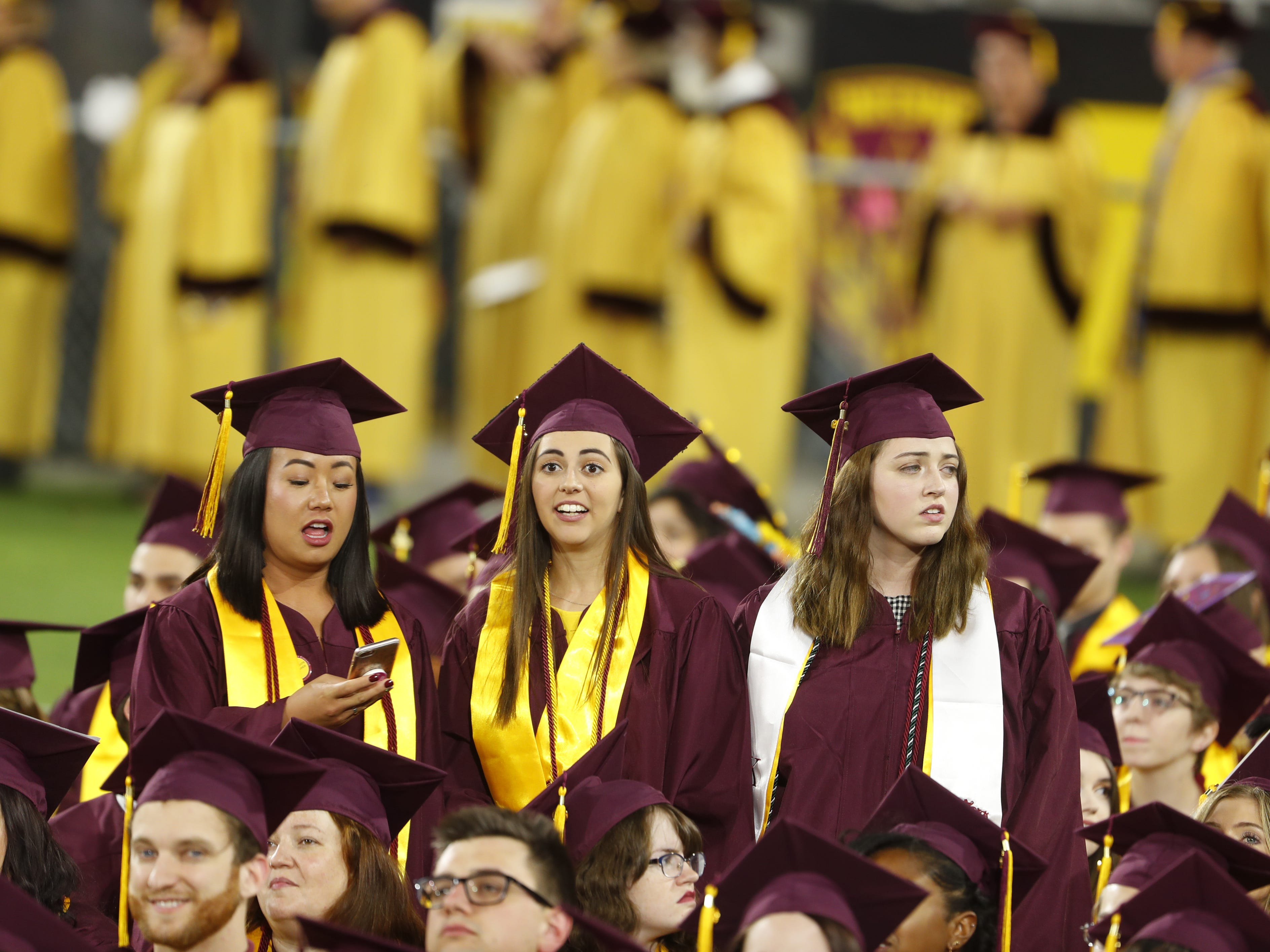 ASU students stand to see over the crowd of caps and gowns during ASU's Undergraduate Commencement at Sun Devil Stadium in Tempe, Ariz. on May 6, 2019.