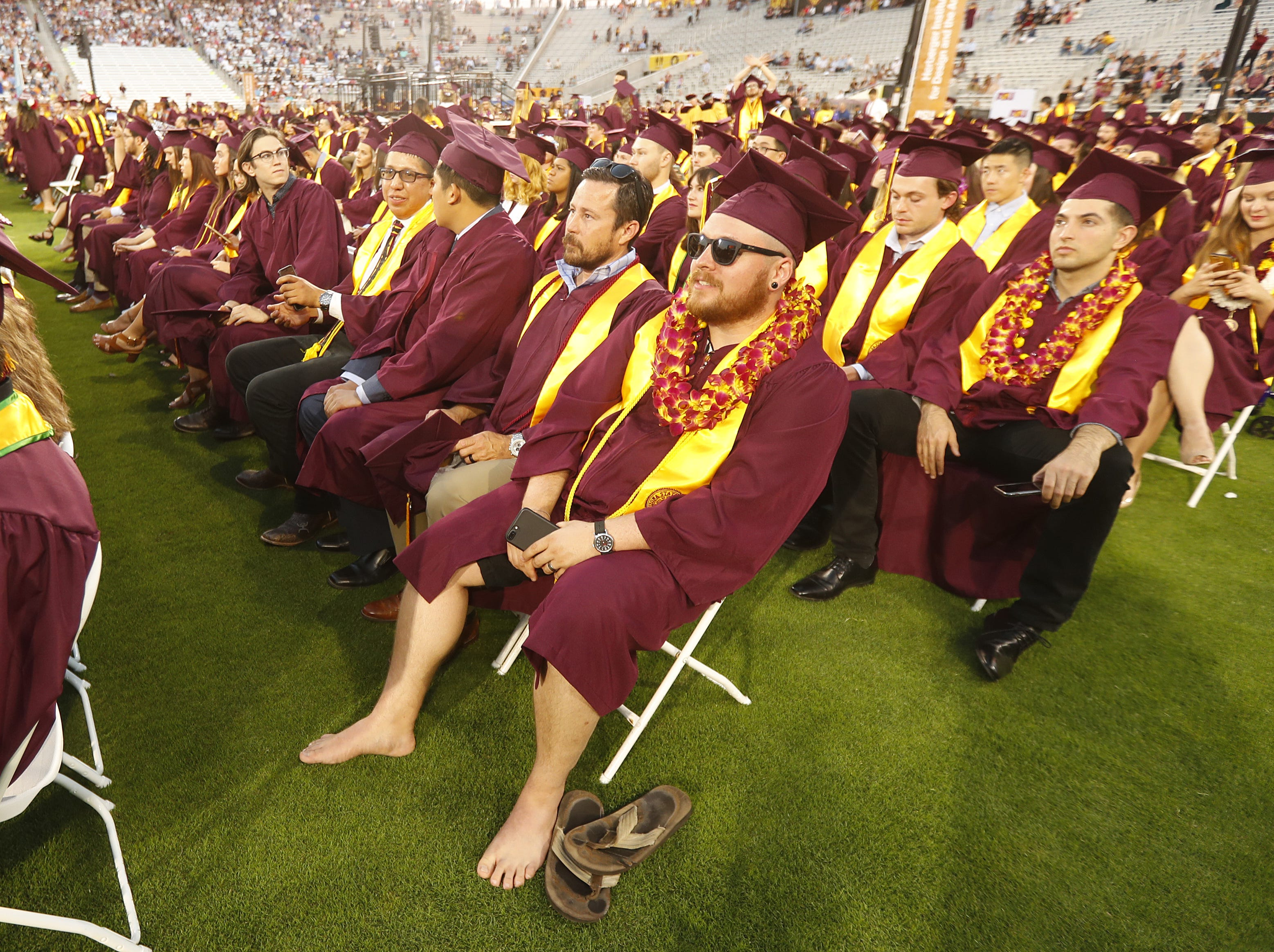 ASU's Matthew Smith gets comfy letting his feet breathe during ASU's Undergraduate Commencement at Sun Devil Stadium in Tempe, Ariz. on May 6, 2019.