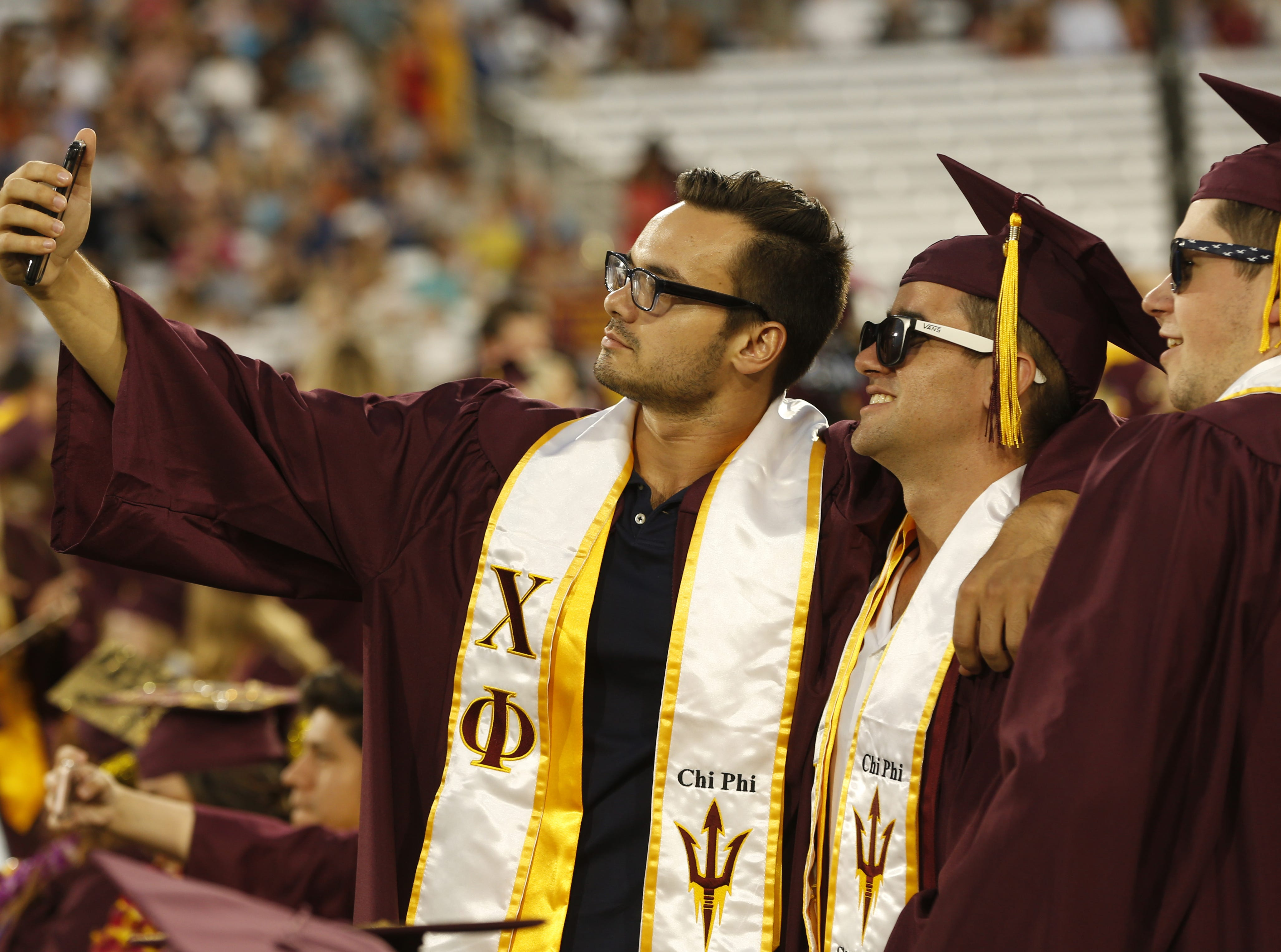 ASU graduates pose for selfies before ASU's Undergraduate Commencement at Sun Devil Stadium in Tempe, Ariz. on May 6, 2019.