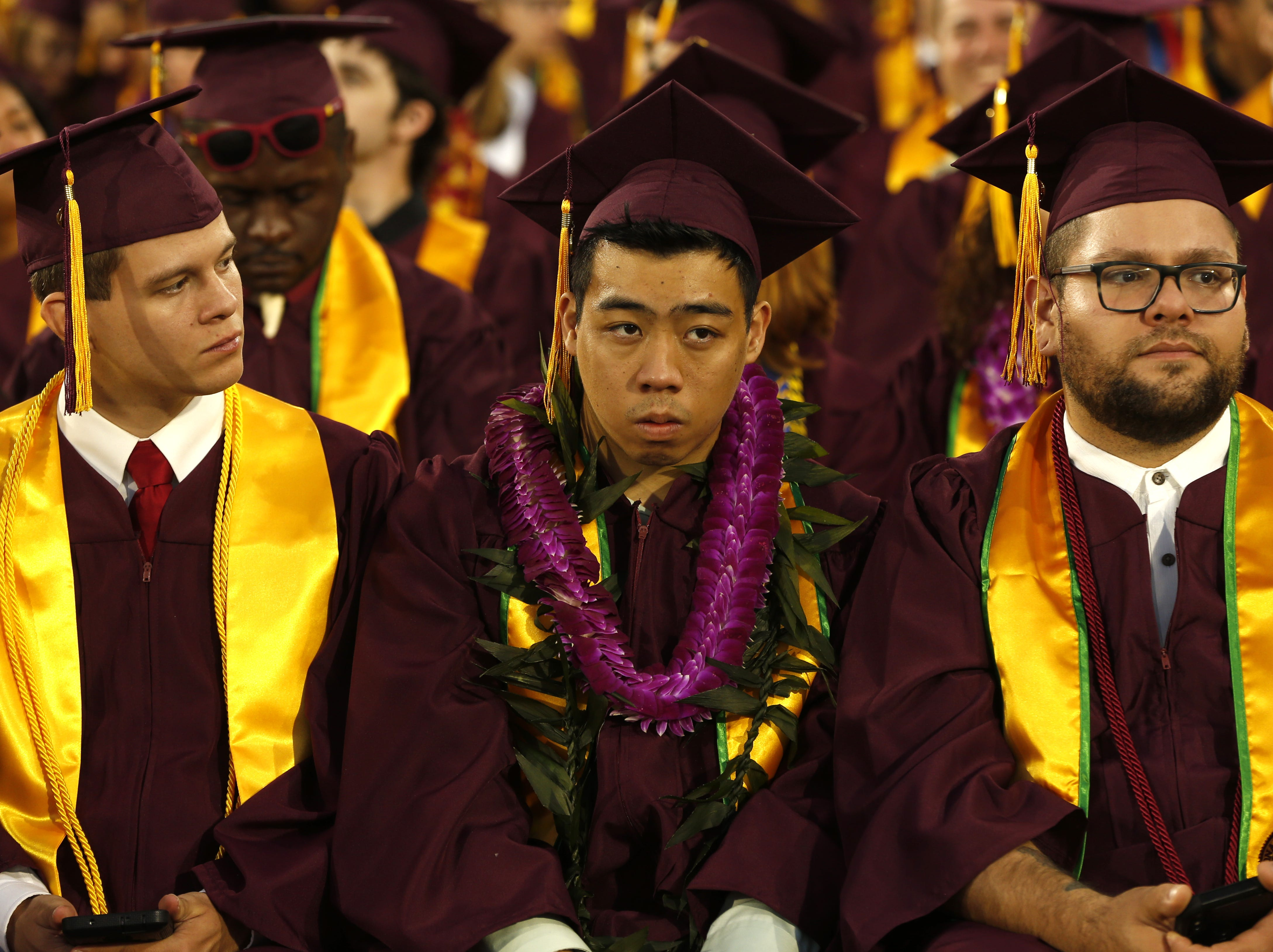 ASU graduates' Joseph Ripsam (L), Dylan La and Dylan Perez wait before ASU's Undergraduate Commencement at Sun Devil Stadium in Tempe, Ariz. on May 6, 2019.