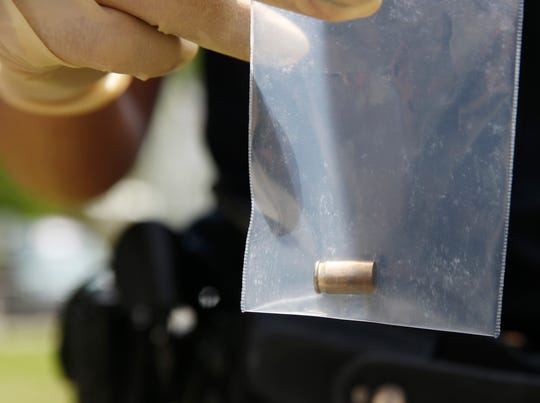 A City of Poughkeepsie Police officer holds a bag with a shell casing from a shooting that occurred at the Hudson Gardens Apartments in the City of Poughkeepsie on May 7, 2019.