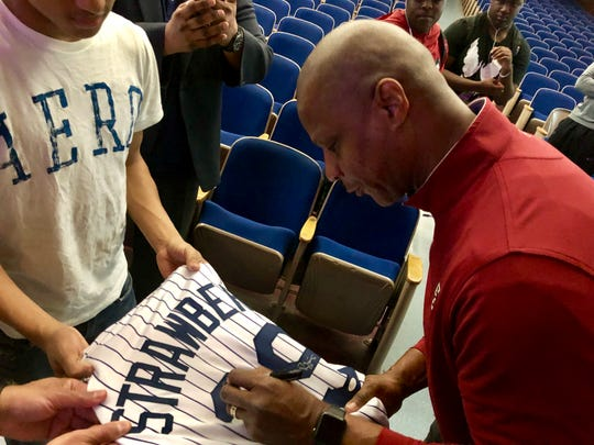 Darryl Strawberry autographs a jersey for Poughkeepsie High School student James Bradshaw.