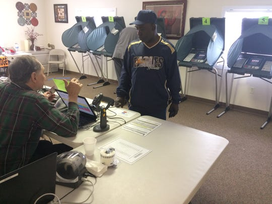 The Rev. Terry L. Gibson checks in Tuesday morning to vote at Mount Olive Baptist Church.