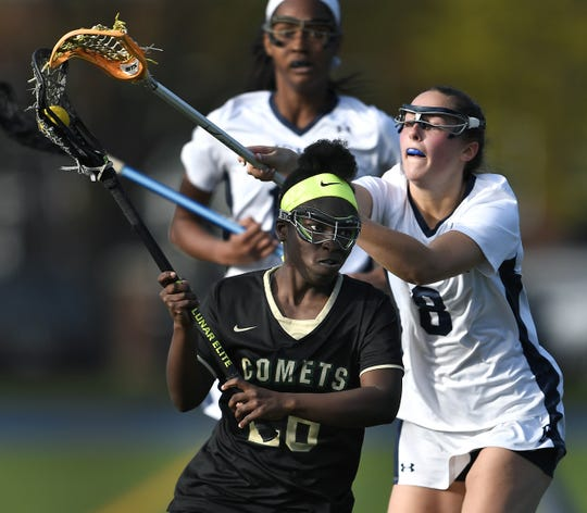 Rush-Henrietta's Lena Cox, left, is pressured from behind by Brighton's Rae Strazdins during a game at Brighton High School, Monday, May 6, 2019. Rush-Henrietta beat Brighton 9-3.