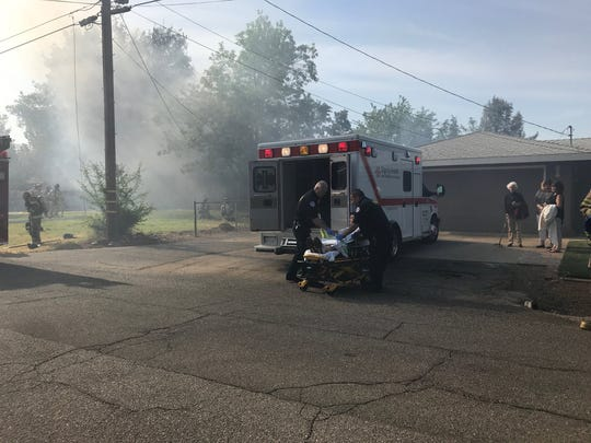 Medics load a patient into an ambulance at a house fire that broke out at a home in east Redding on Tuesday morning.