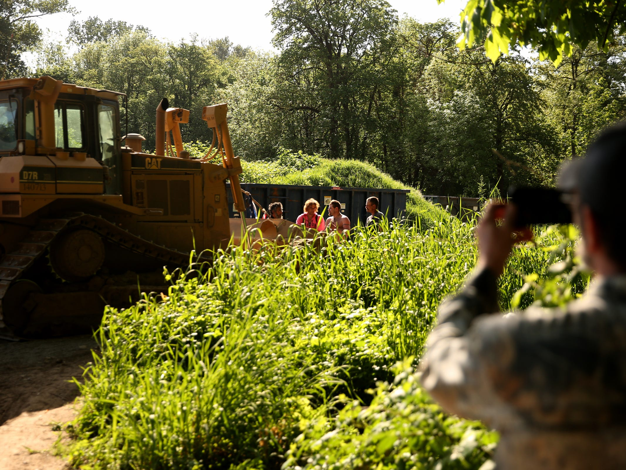 Art Scaglione, a volunteer and advocate for the homeless, takes photos as several people stand in front of a bulldozer coming onto a privately-owned rock quarry with a homeless camp near Wallace Marine Park in West Salem on May 7, 2019. Signs were posted throughout the camp recently stating personal property must be removed or it will be taken by the landowner and its designated agent starting May 7. An eviction can't be enforced until a court approves it.