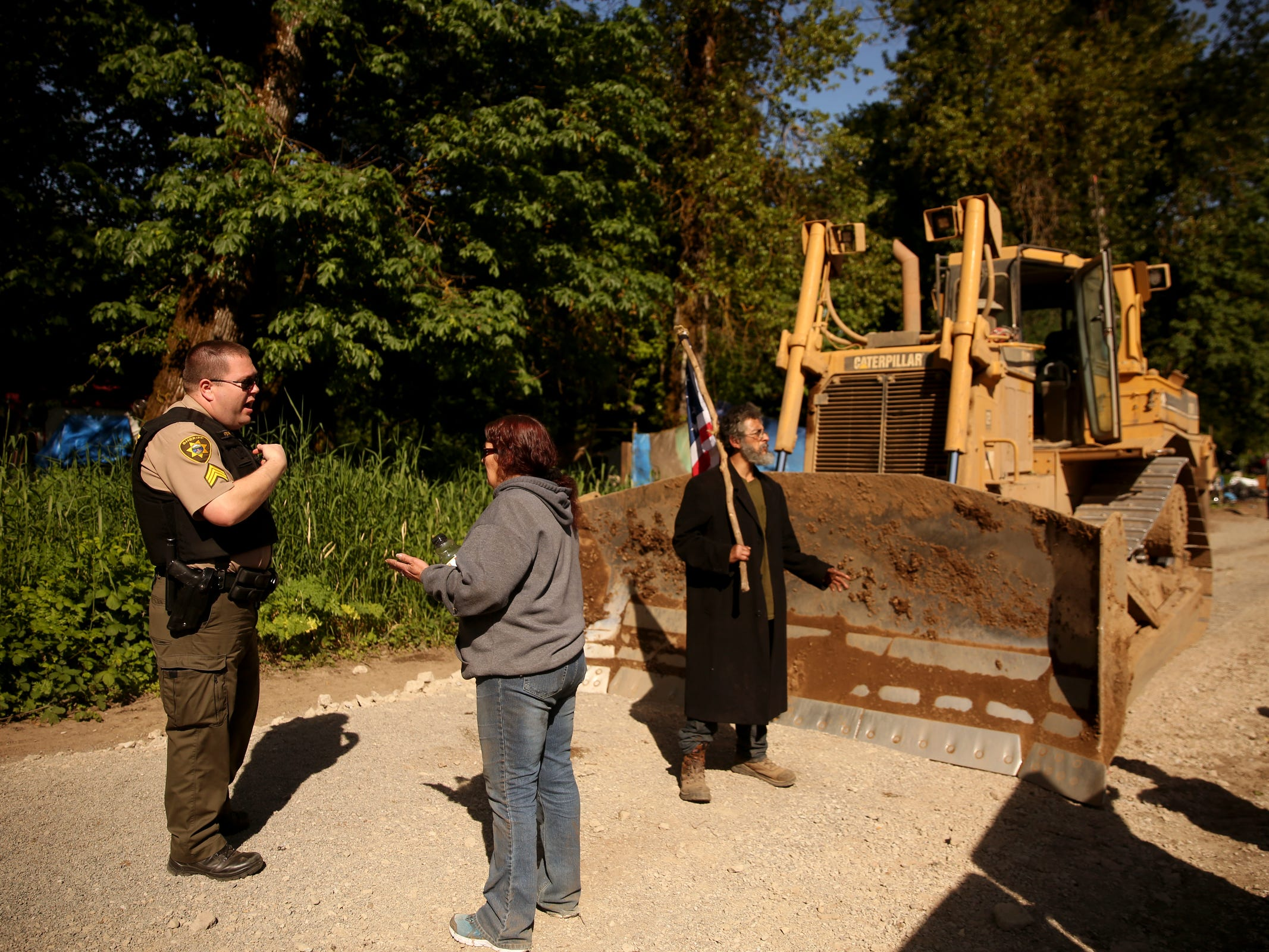 Sgt. Todd Fenk, with the Polk County Sheriff's Office, talks with Joan Tomlinson after several people stood in front of a bulldozer that came into a privately-owned rock quarry with a homeless camp near Wallace Marine Park in West Salem on May 7, 2019. Signs were posted throughout the camp recently stating personal property must be removed or it will be taken by the landowner and its designated agent starting May 7. An eviction can't be enforced until a court approves it.