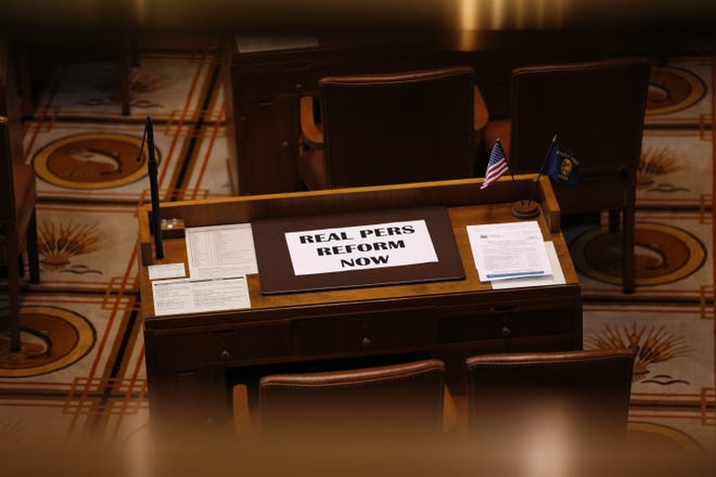 A sign reading 'Real PERS Reform Now' lies on the empty desk of a Republican senators after they didn't show up for Senate floor session at the Oregon State Capitol in Salem on May 7, 2019.