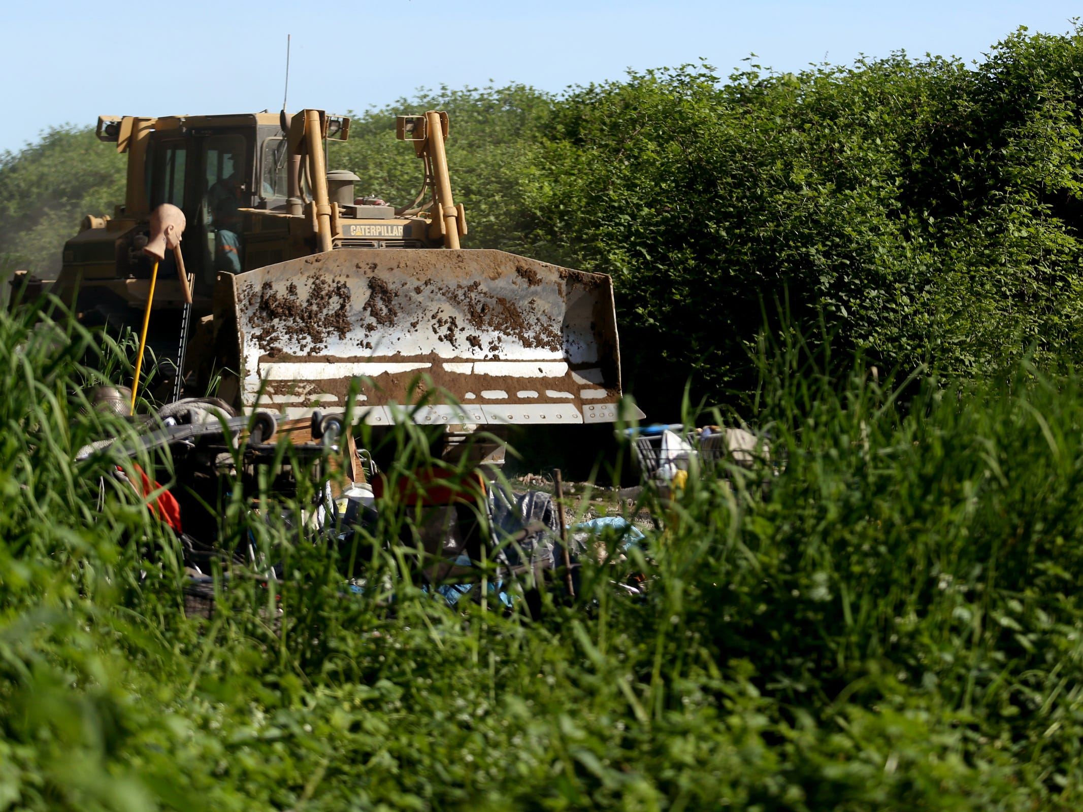 As a bulldozer comes in to a privately-owned rock quarry with a homeless camp near Wallace Marine Park in West Salem on May 7, 2019. Signs were posted throughout the camp recently stating personal property must be removed or it will be taken by the landowner and its designated agent starting May 7. An eviction can't be enforced until a court approves it.