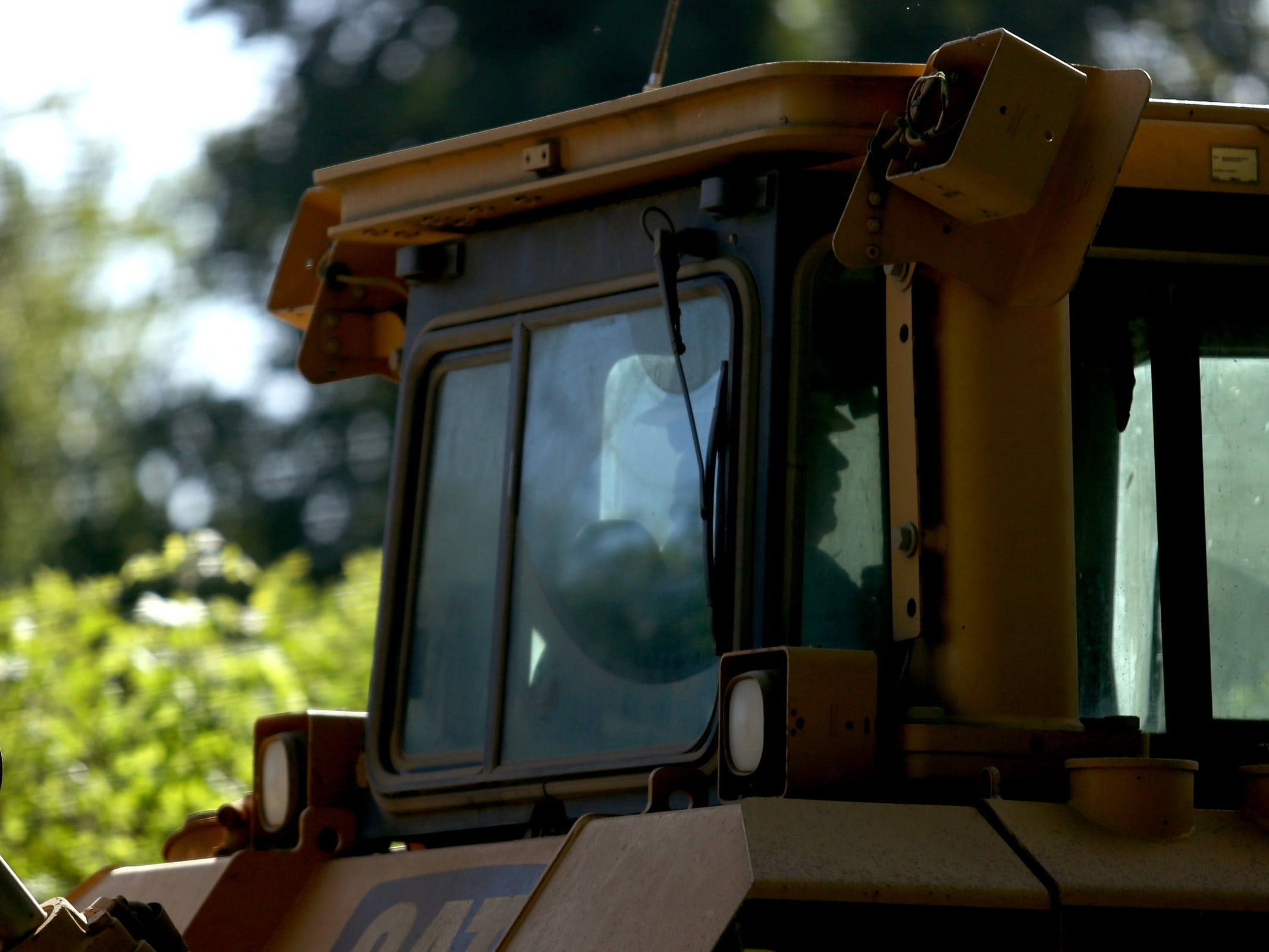 A bulldozer comes in to a privately-owned rock quarry with a homeless camp near Wallace Marine Park in West Salem on May 7, 2019. Signs were posted throughout the camp recently stating personal property must be removed or it will be taken by the landowner and its designated agent starting May 7. An eviction can't be enforced until a court approves it.