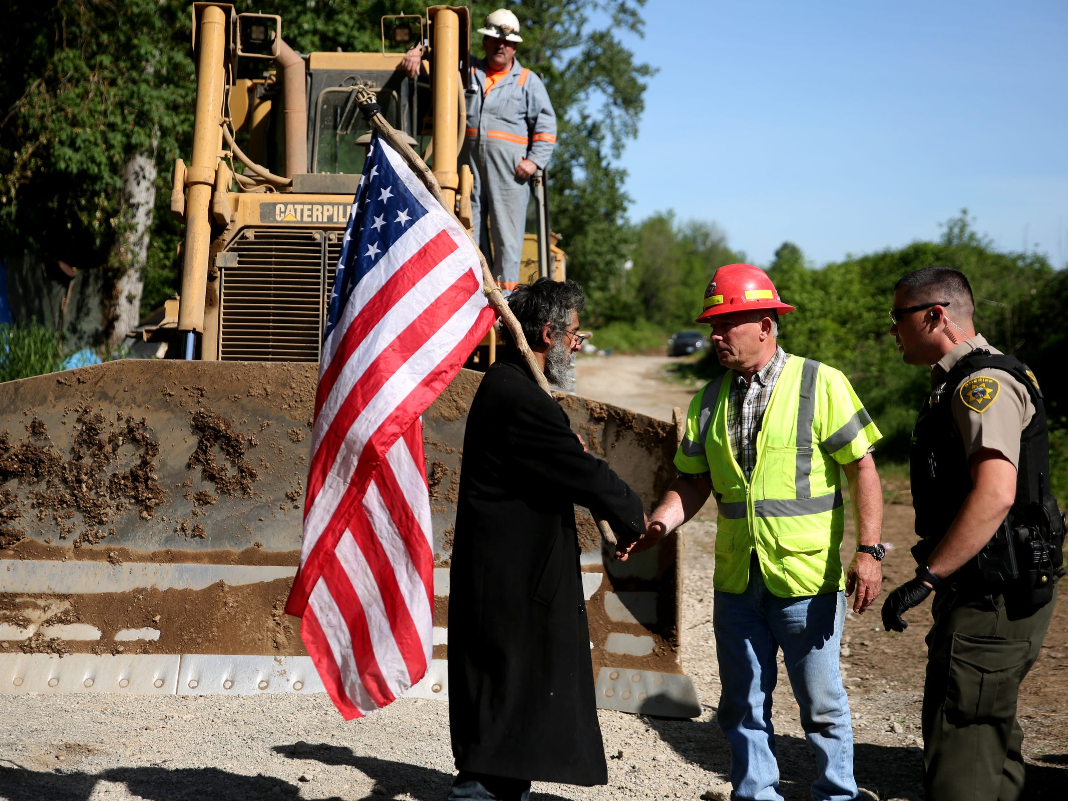 A man living at the homeless camp and a rock quarry employee shake hands after tensions were calmed after several people stood in front of a bulldozer came into a privately-owned rock quarry with a homeless camp near Wallace Marine Park in West Salem on May 7, 2019. Signs were posted throughout the camp recently stating personal property must be removed or it will be taken by the landowner and its designated agent starting May 7. An eviction can't be enforced until a court approves it.