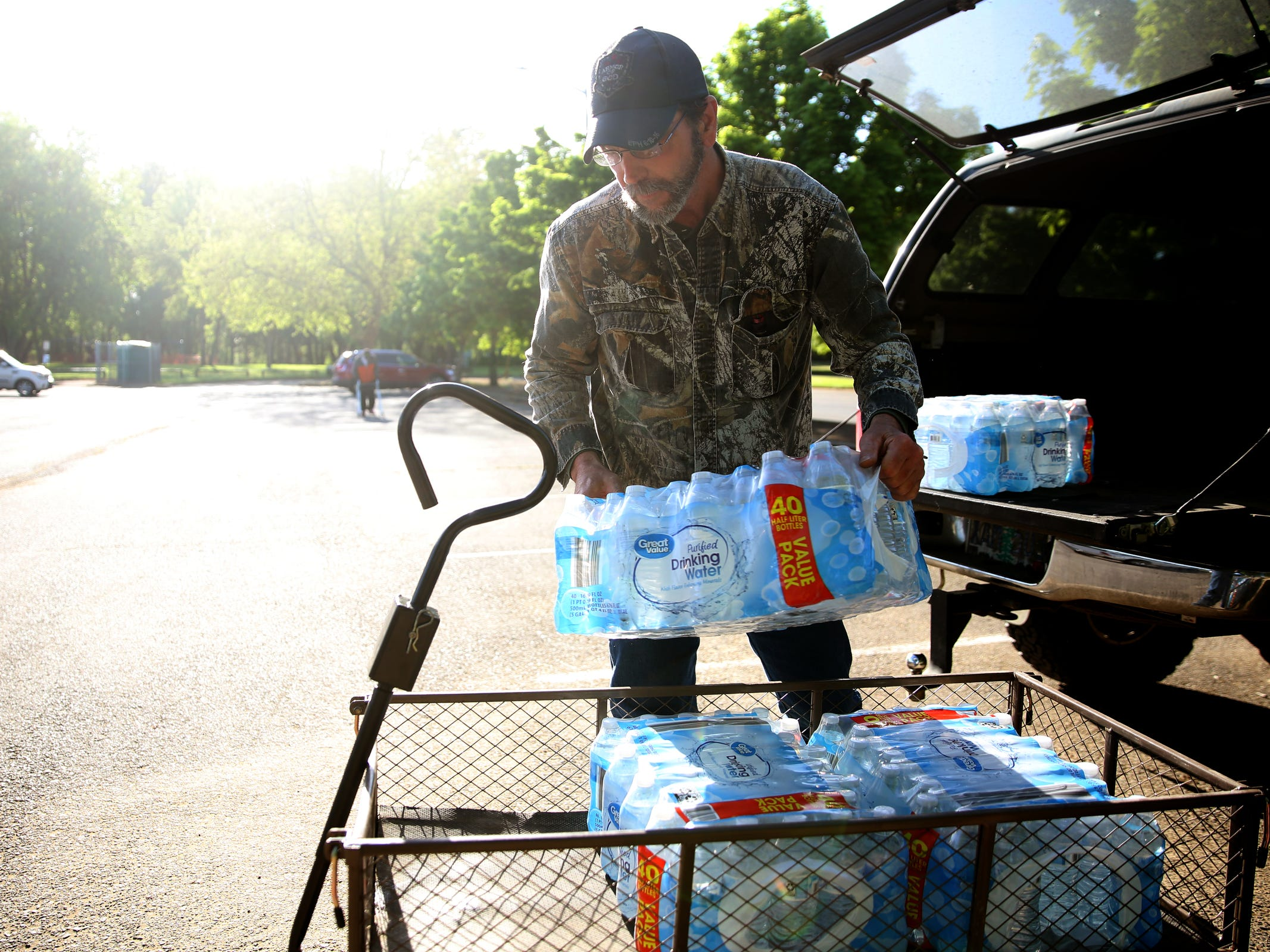 Art Scaglione, a volunteer and advocate for the homeless, loads up cases of water to bring into a homeless camp near Wallace Marine Park in West Salem on May 7, 2019. Signs were posted throughout the camp recently stating personal property must be removed or it will be taken by the landowner and its designated agent starting May 7. An eviction can't be enforced until a court approves it.