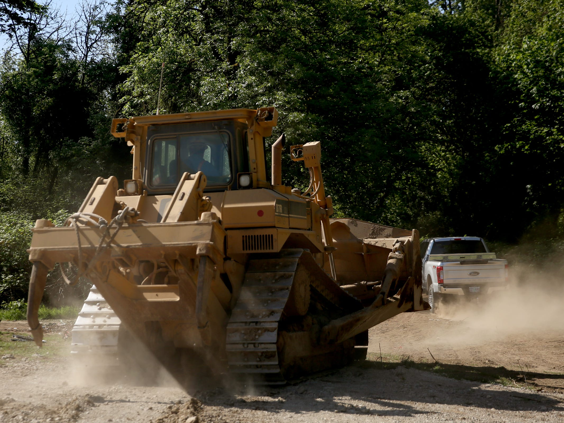 As a bulldozer drives away after several people stood in front of it to block it when it came into a privately-owned rock quarry with a homeless camp near Wallace Marine Park in West Salem on May 7, 2019. Signs were posted throughout the camp recently stating personal property must be removed or it will be taken by the landowner and its designated agent starting May 7. An eviction can't be enforced until a court approves it.