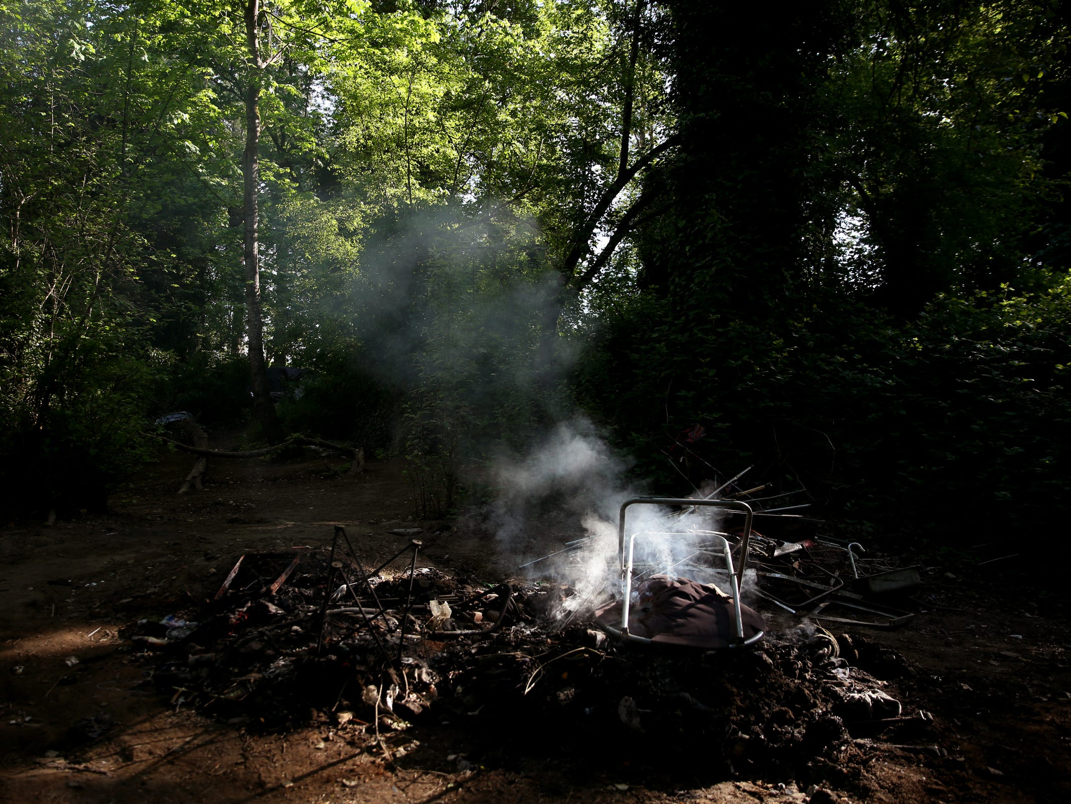 A fire smokes in a homeless camp near Wallace Marine Park in West Salem on May 7, 2019. Signs were posted throughout the camp recently stating personal property must be removed or it will be taken by the landowner and its designated agent starting May 7. An eviction can't be enforced until a court approves it.