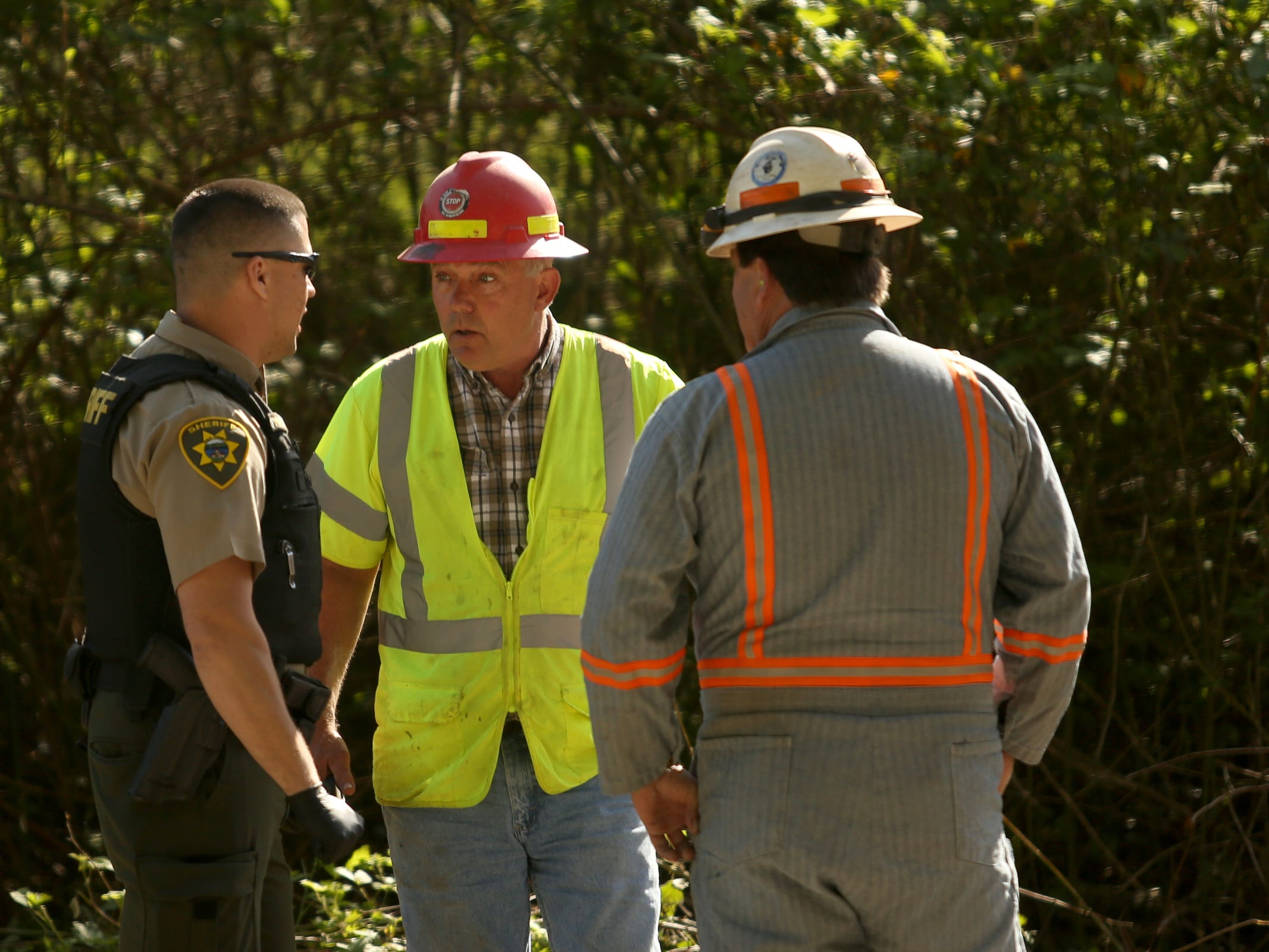 Rock quarry employees and law enforcement talk after a bulldozer came into a privately-owned rock quarry with a homeless camp near Wallace Marine Park in West Salem on May 7, 2019. Signs were posted throughout the camp recently stating personal property must be removed or it will be taken by the landowner and its designated agent starting May 7. An eviction can't be enforced until a court approves it.