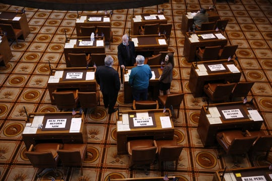 A group including three Democratic senators stand among the empty desks of Republican senators during a Senate floor session at the Oregon State Capitol in Salem on May 7, 2019.