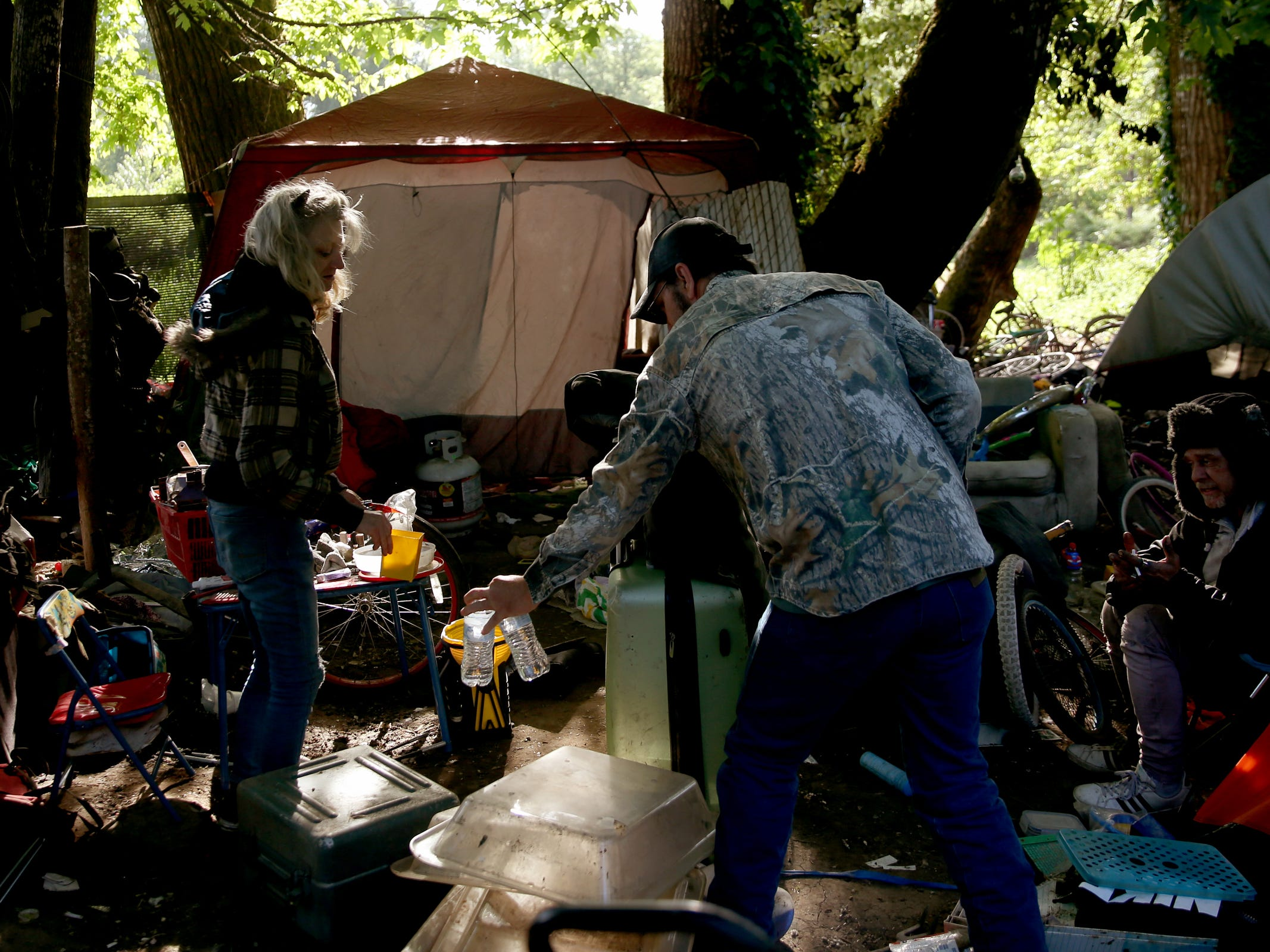Art Scaglione, a volunteer and advocate for the homeless, brings bottles of water into a homeless camp near Wallace Marine Park in West Salem on May 7, 2019. Signs were posted throughout the camp recently stating personal property must be removed or it will be taken by the landowner and its designated agent starting May 7. An eviction can't be enforced until a court approves it.